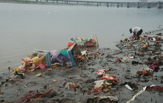 Worker trying to clean up the bank of river post immersion activities