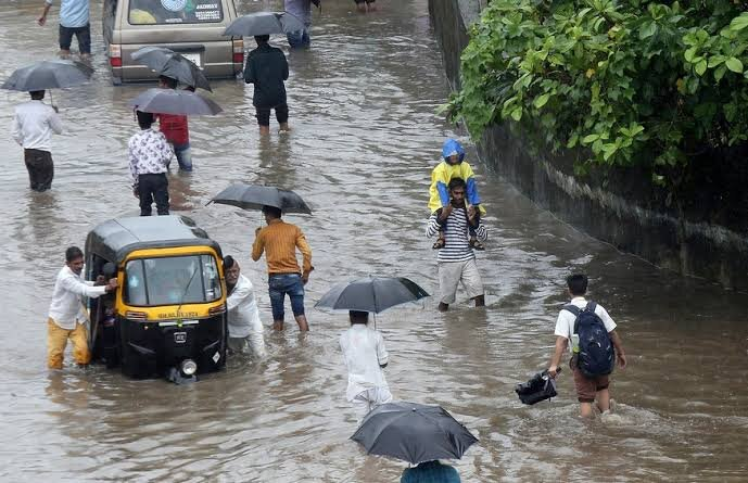 People wading through a flooded street with some dragging an auto along and a man carrying his child on his shoulders to keep him away from the floods