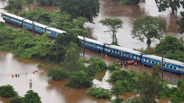 An Indian railways train stuck midway due to rising flood levels, while the NDRF rescue passangers