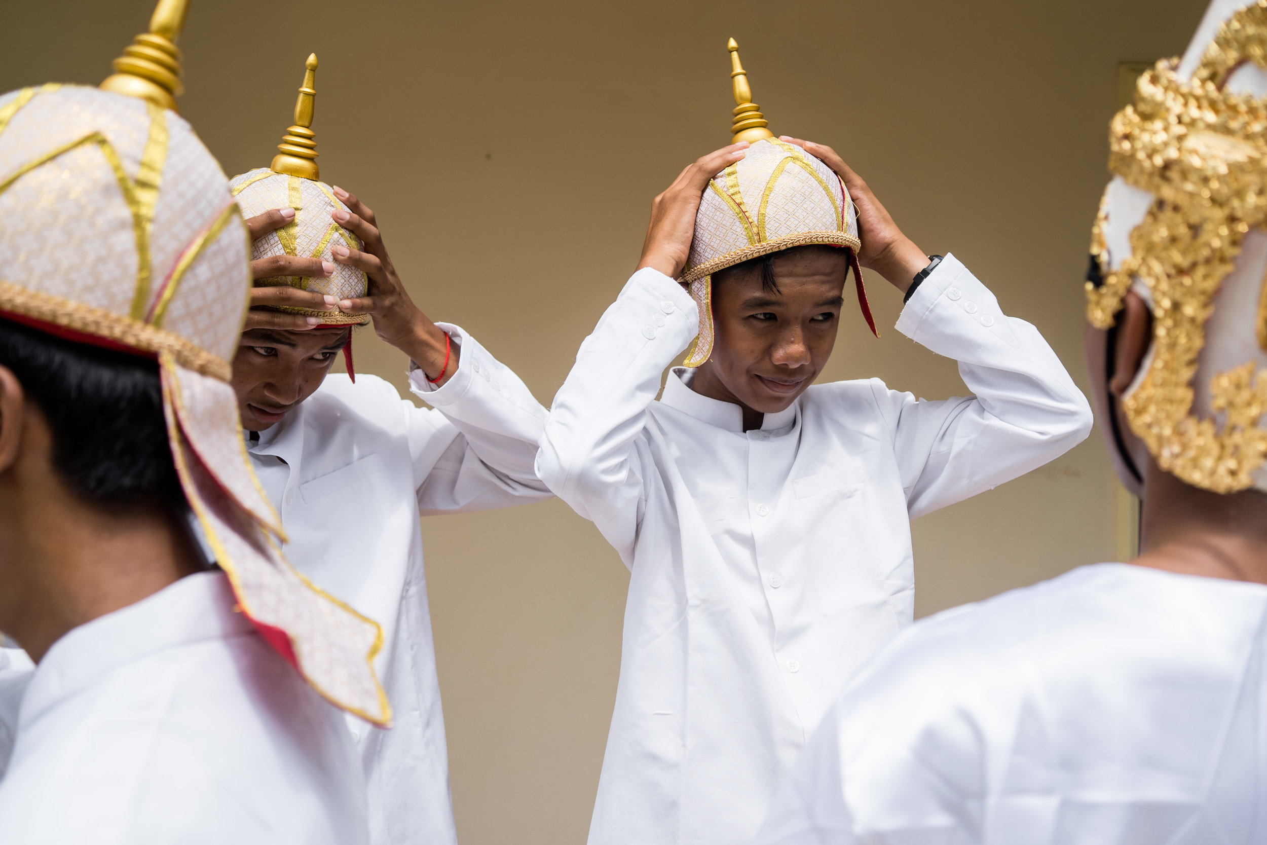 Young men adjust their headdresses in preparation for a procession on Visak Bochea Day, a Buddhist holiday that celebrates the birth, enlightenment, and death of Buddha