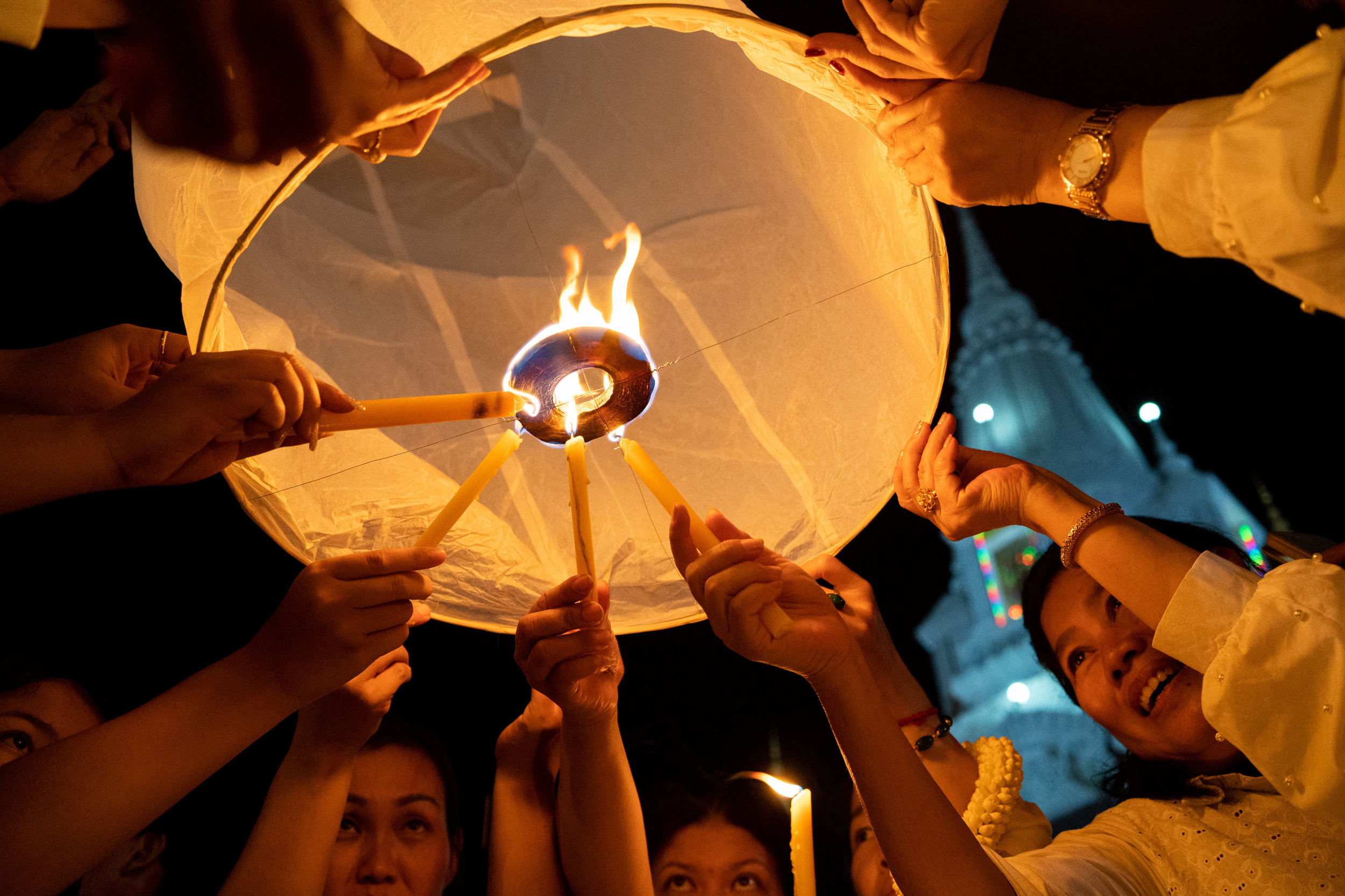 Women light sky lanterns for Meak Bochea Day at Kol Tor Teng Pagoda in Phnom Penh. The holiday takes place under the full moon in the third month of the Khmer lunar calendar and commemorates the ordainment of Buddha's first 1250 disciples