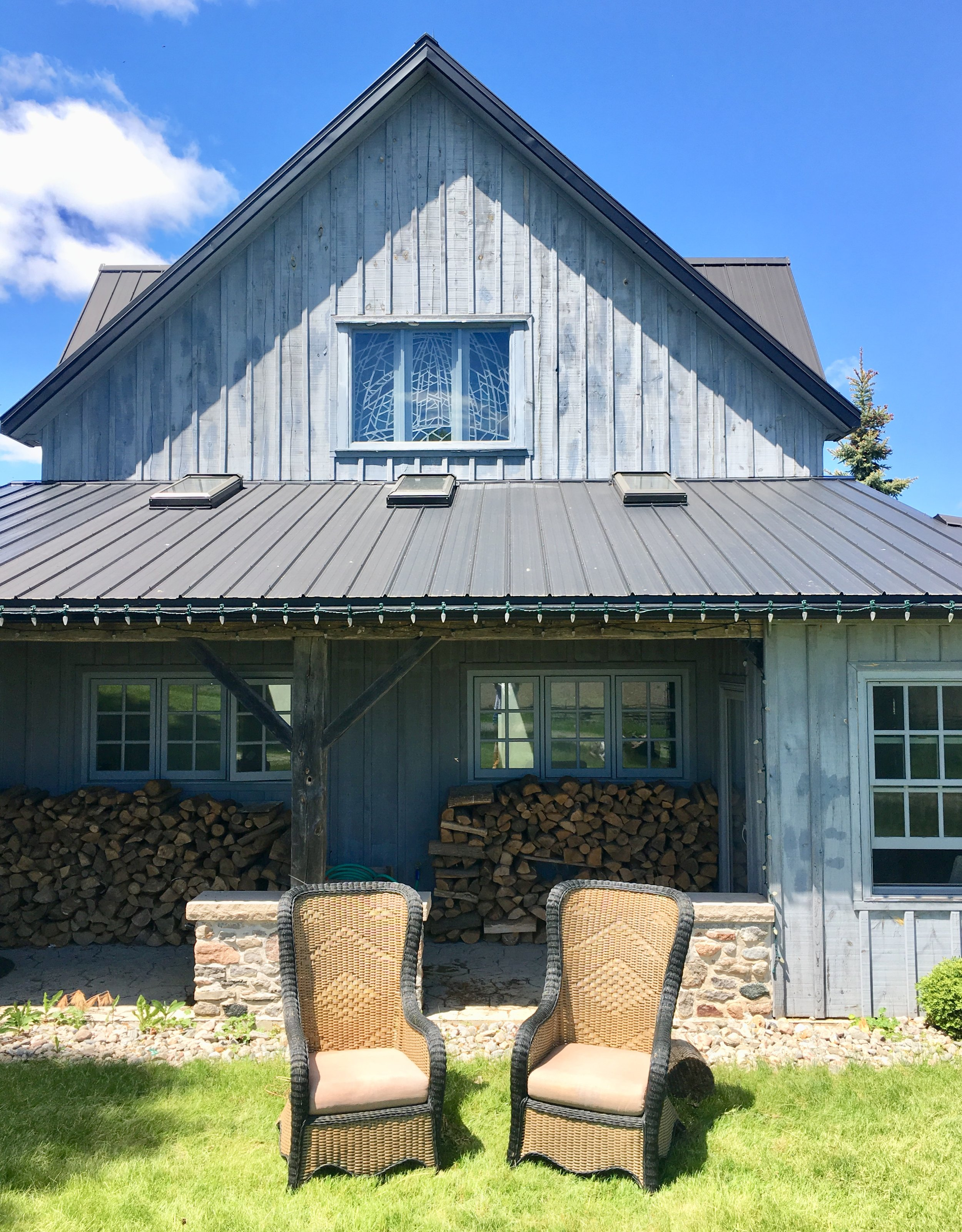 This is the South-facing view of the board-and-batten addition to Drumlin Farmhouse. This exterior shot shows the stained glass window and skylights that we will be making more of a focal point as part of the kitchen renovation. You can also see the sunroom to the right of the stacked firewood.