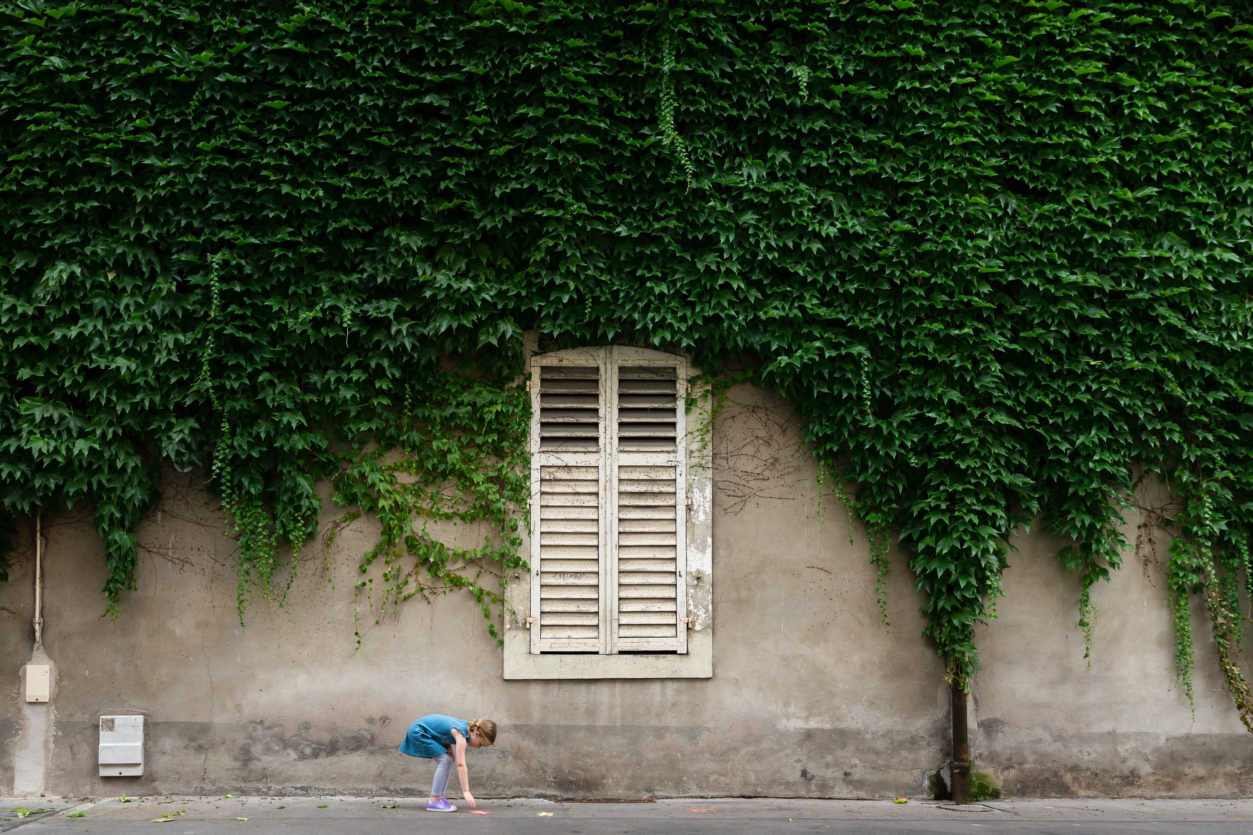 girl_picking_up_flyer_under_ivy_and_white_shutters_in_france_Personal_portfolio_by_rebecca_hunnicutt_farren.jpg