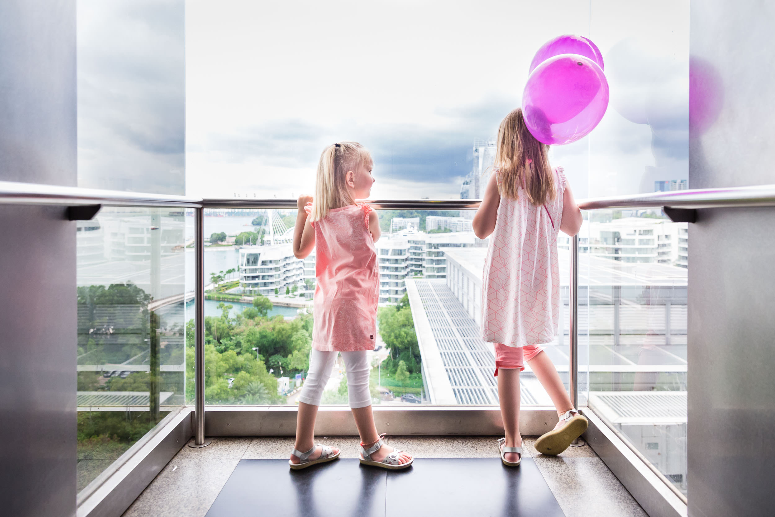 sisters_wearing_pink_holding_baloons_in_elevator_in_singapore_Personal_portfolio_by_rebecca_hunnicutt_farren.jpg