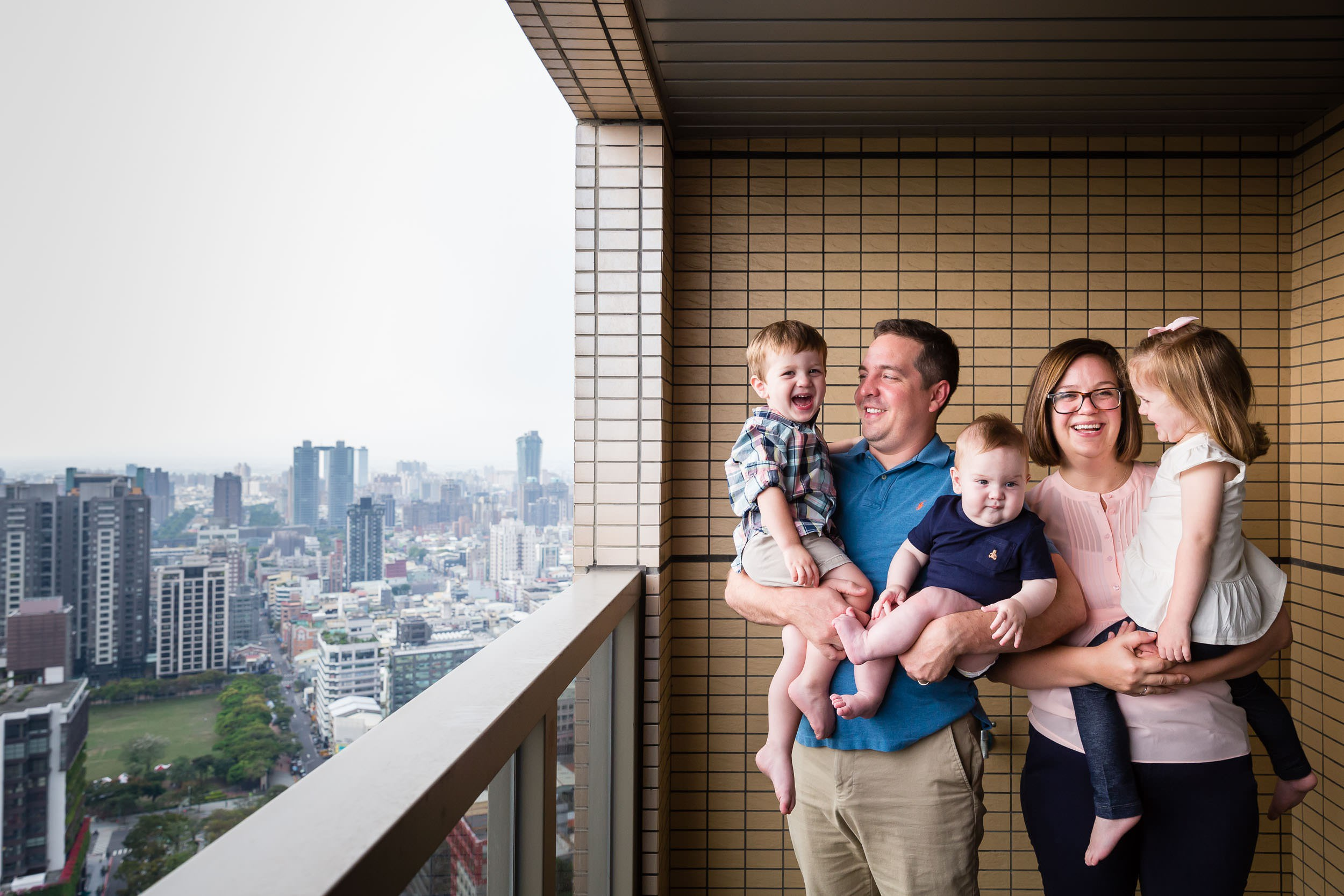 Image of a family of five on their high rise apartment balcony, in Taichung Taiwan, by Rebecca Hunnicutt Farren of Hunnicutt Photography.