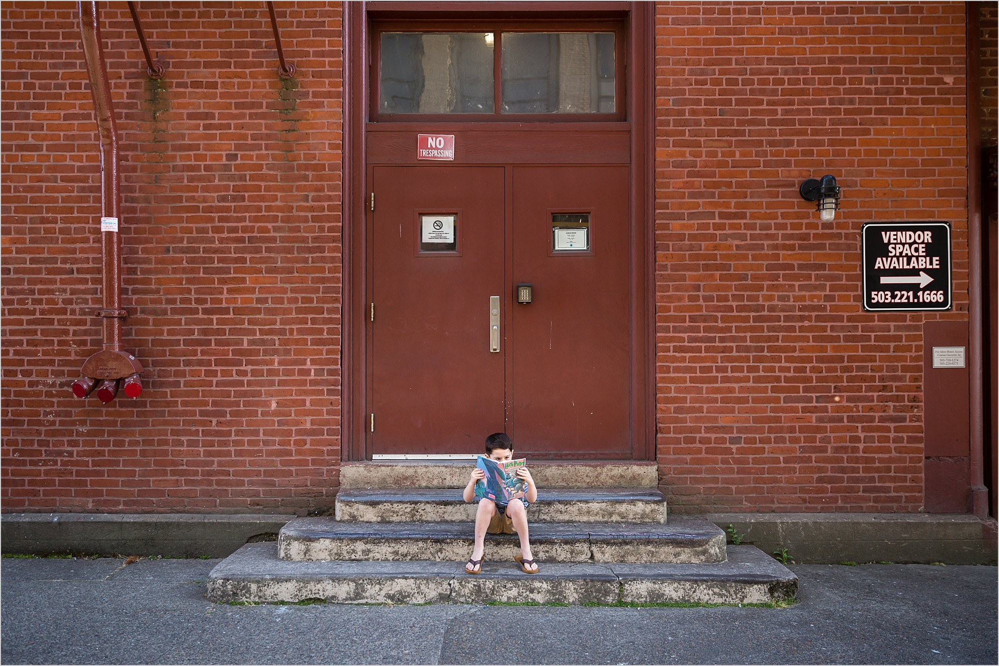 boy reading harry potter book sitting on steps in downtown portland oregon modern urban family lifestyle photo session hunnicutt photography
