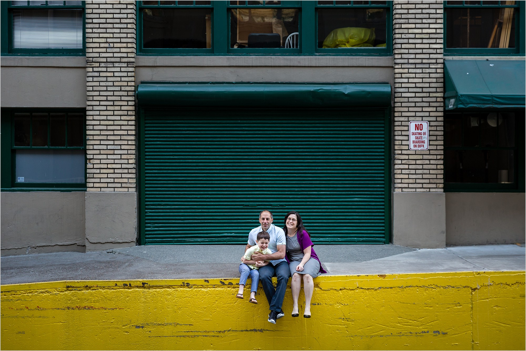 family sitting on yellow wall by green door in portland oregon for urban modern family portraits by hunnicutt photography