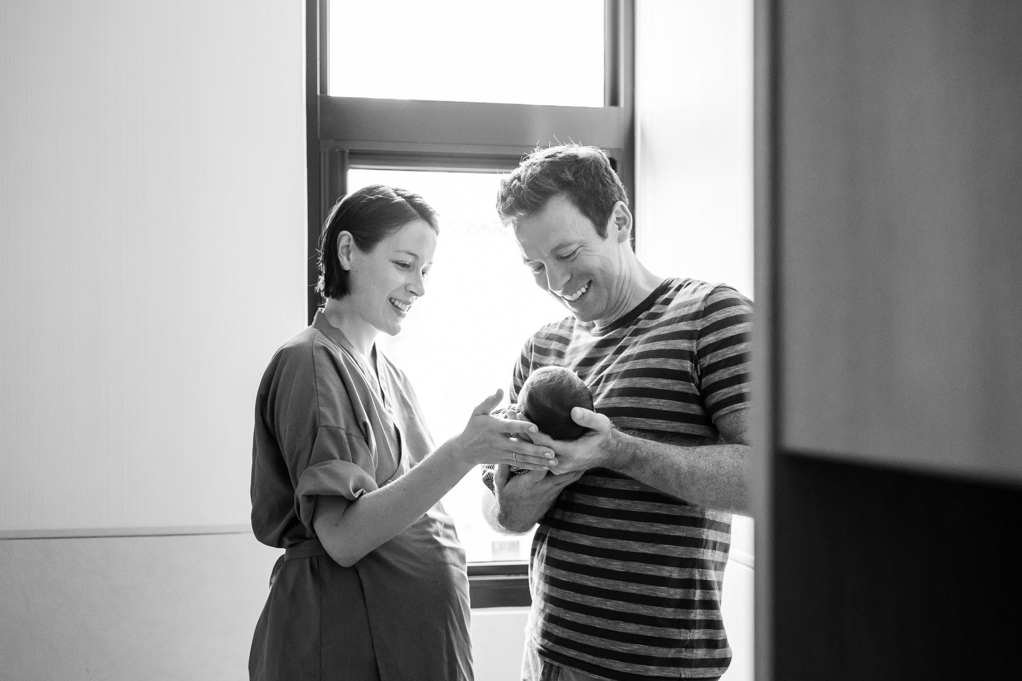 monochrome image of smiling parents holding newborn baby in the hospital after birth at a fresh 48 birth space newborn photography session in portland oregon  by hunnicutt photography