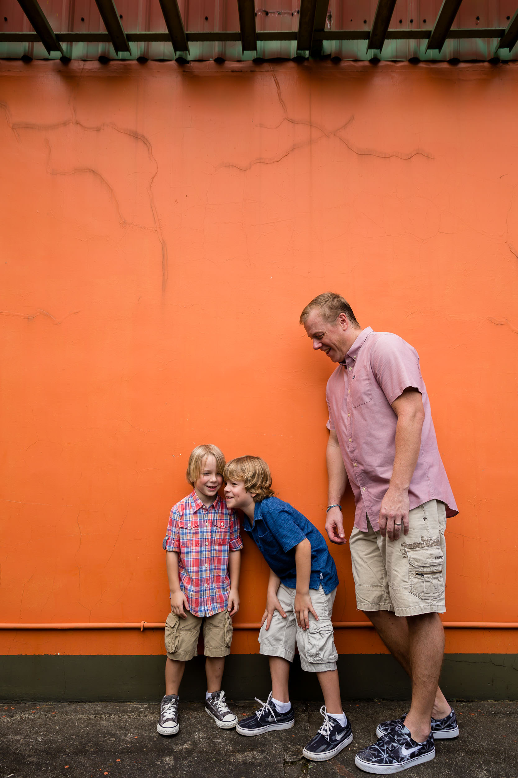 father and two boys standing by orange wall by hunnicutt photography in portland oregon, pacific northwest family and child photography