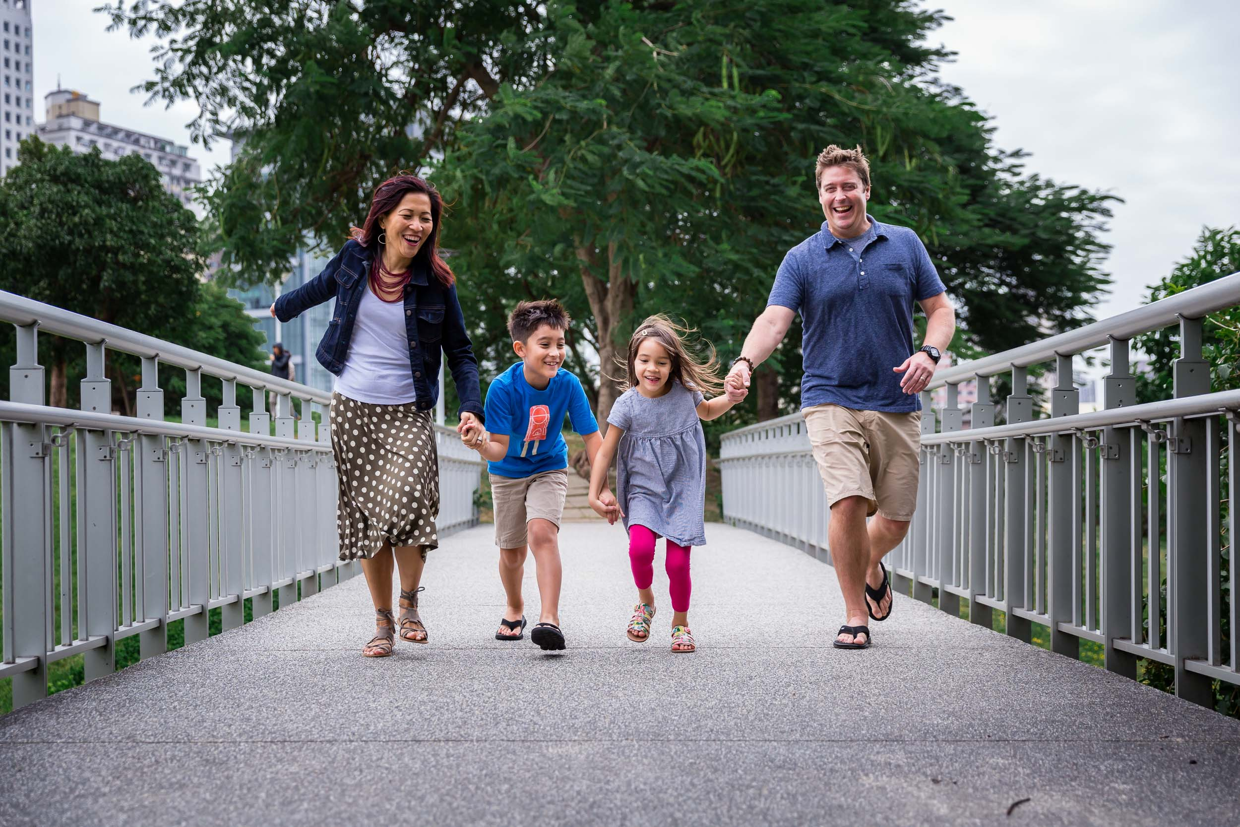 family holding hands and running and having fun on a bridge by hunnicutt photography, portland oregon family urban lifestyle photographer