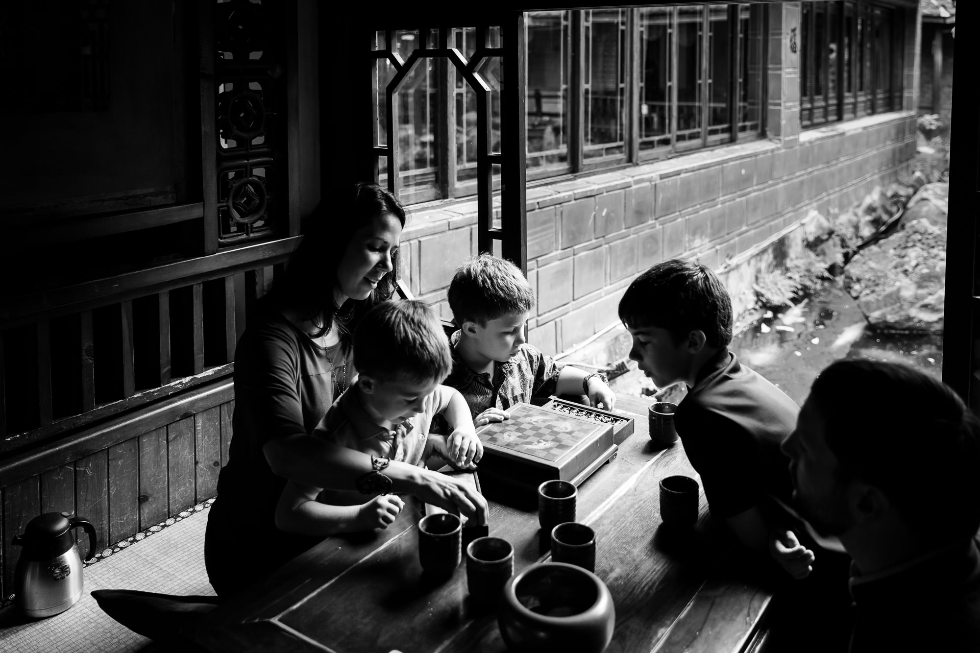 monochrome image of family playing chess in a traditional tea shop by hunnicutt photography portland oregon premiere family photographer