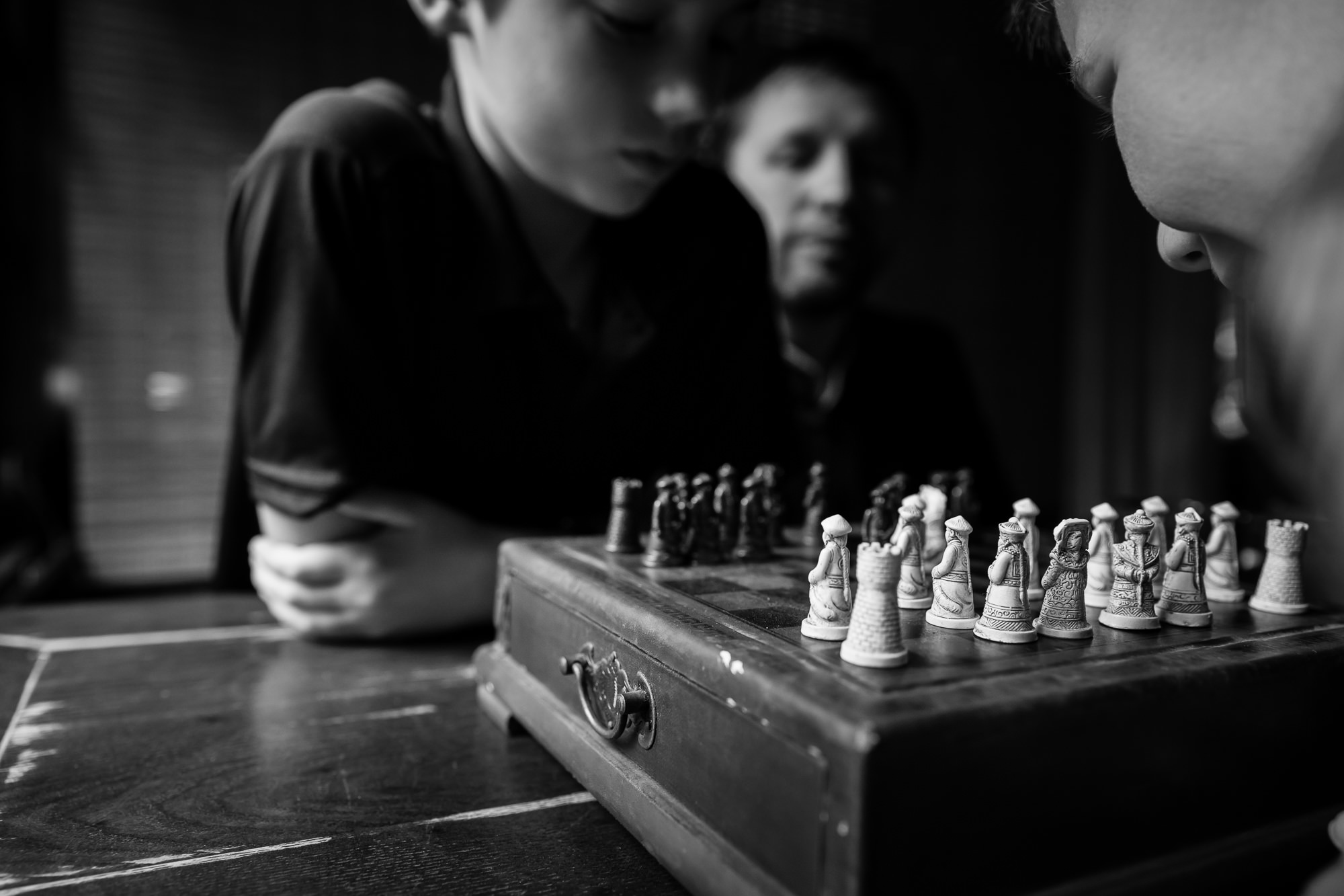 monochrome image of kids playing chess on chinese style chess board by hunnicutt photography