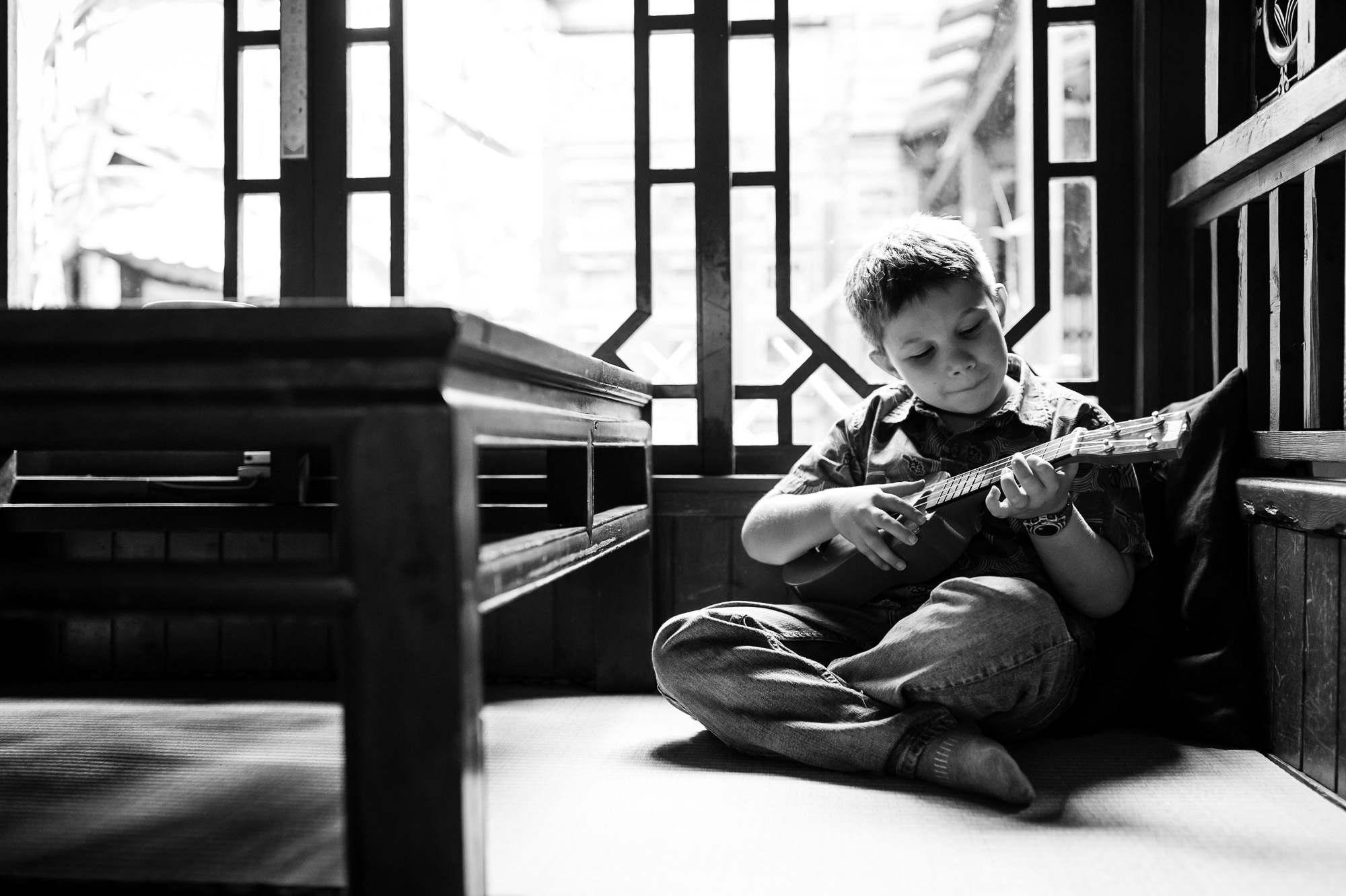 monochrome image of boy playing ukulele by rebecca hunnicutt farren portland oregon childrens photographer