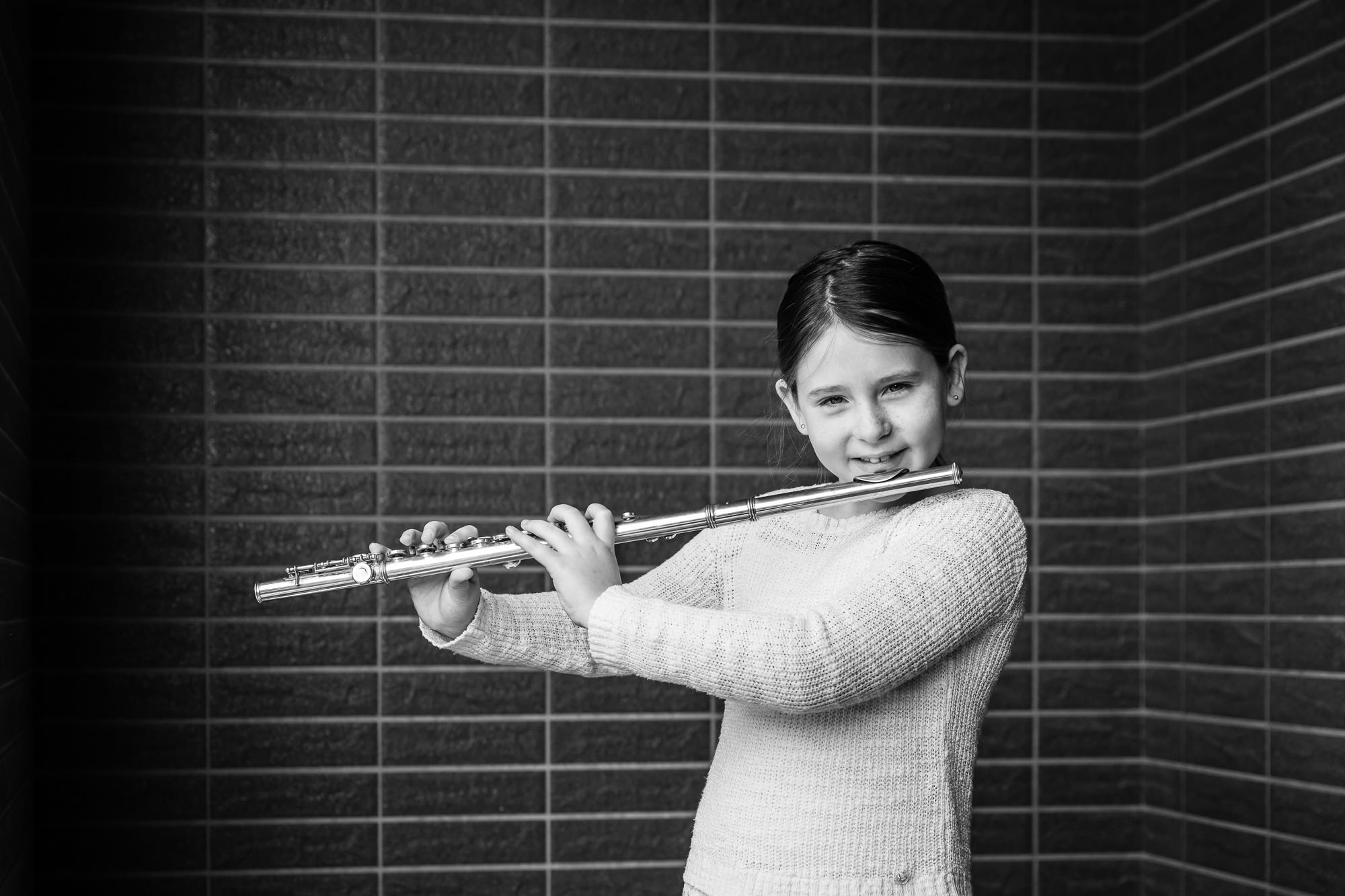 monochrome image of girl smiling holding flute by rebecca hunnicutt farren, portland oregons premiere childrens photographer