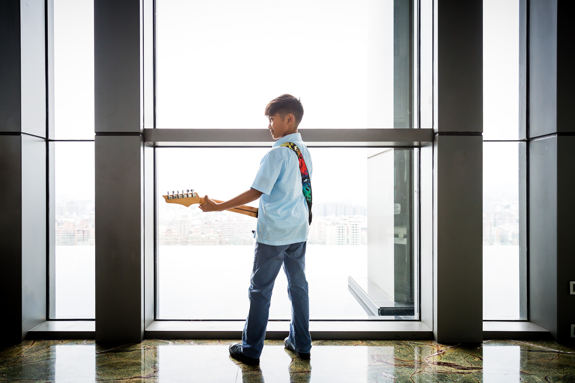boy in blue holding bass guitar by large window by hunnicutt photography in portland oregon