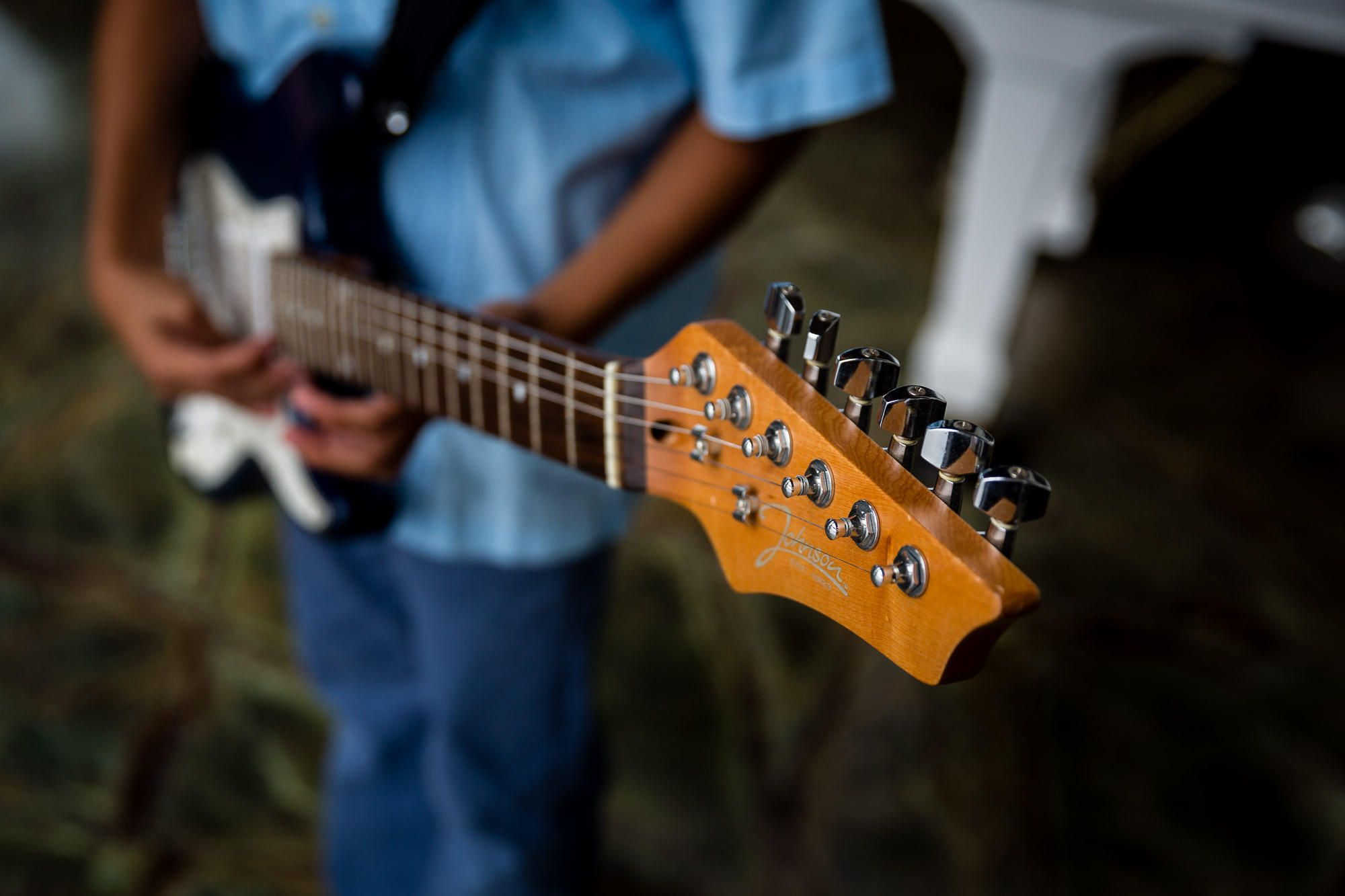 detail image of boy holding bass guitar by hunnicutt photography