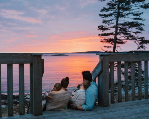 Family watching sunset over the ocean at Oceanstone Resort near Peggy's Cove, Nova Scotia. Image Credit:  The Wild Decoelis