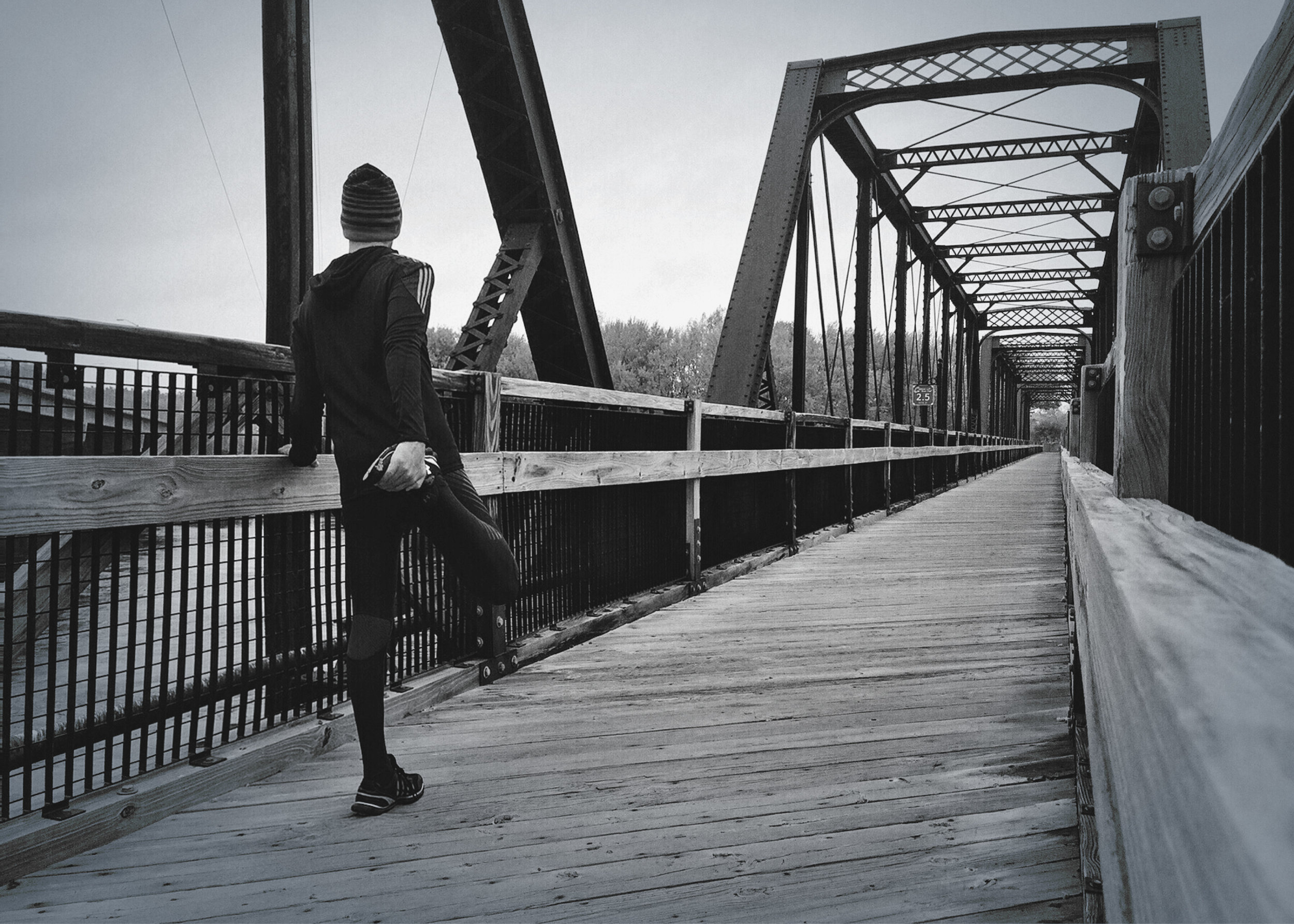 Runner stretching on a wooden bridge