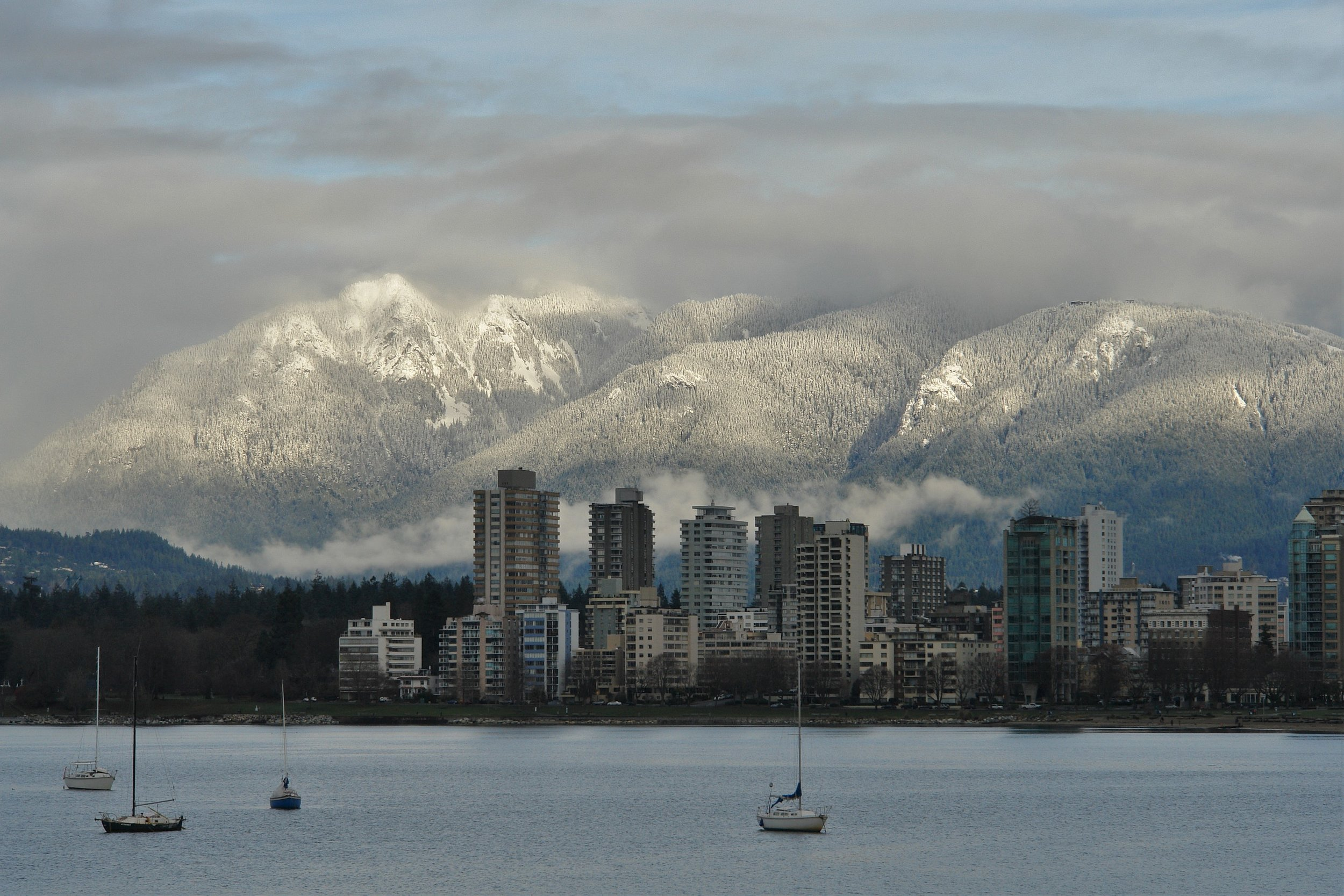 Waterfront view of Vancouver buildings with mountains in the background