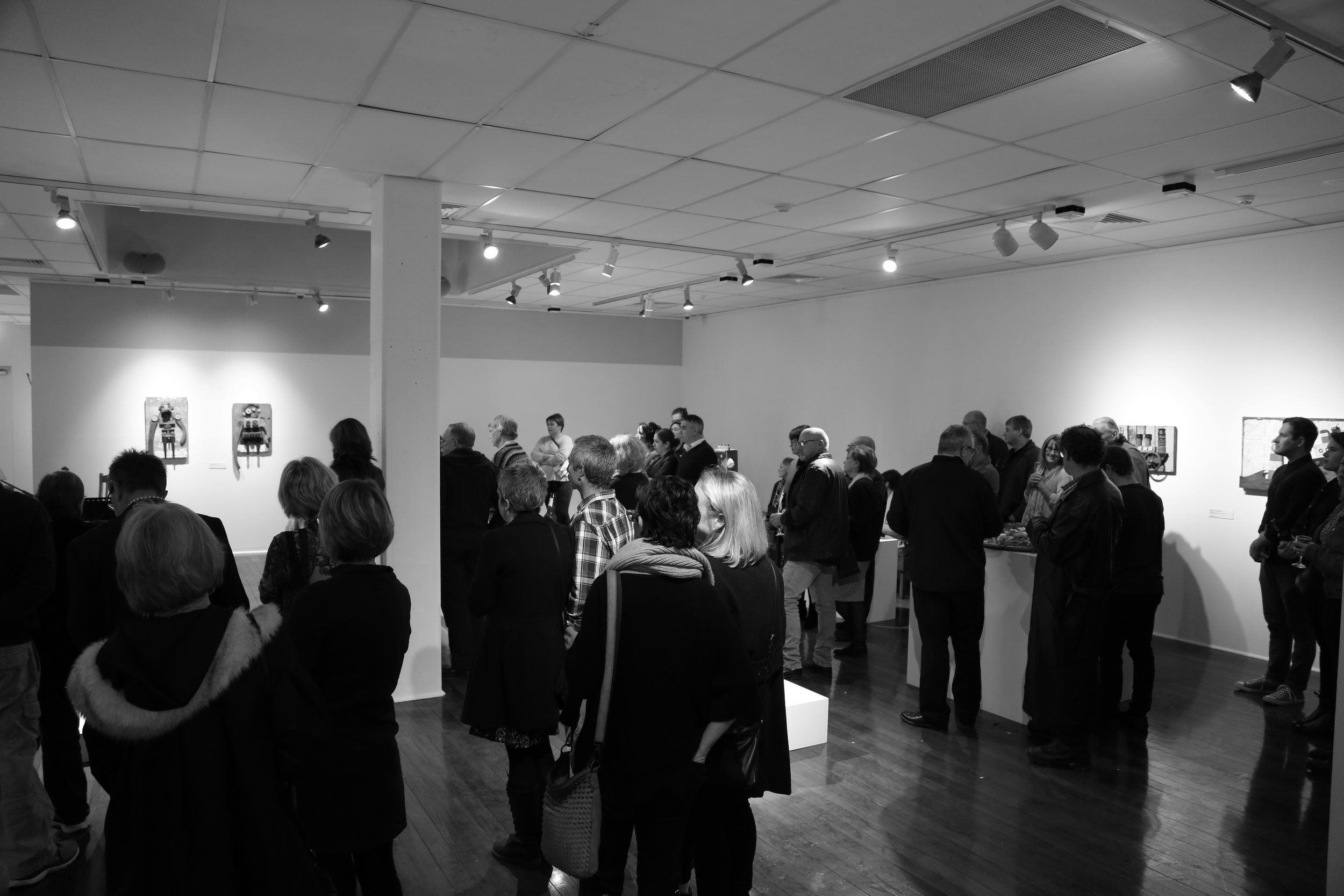 People listening to speeches at an art gallery opening night
