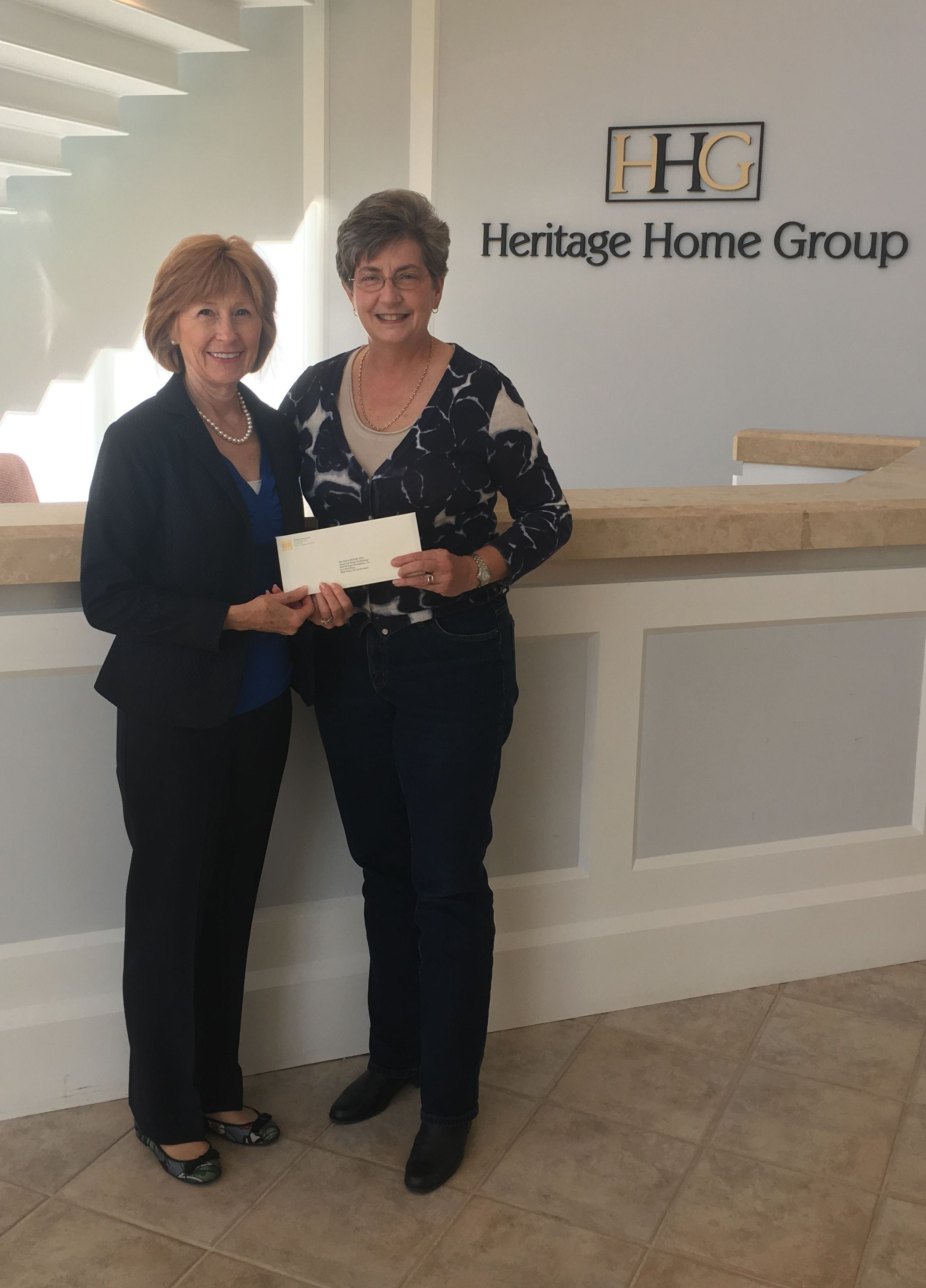 Karen McNeill, CEO of the American Home Furnishings Hall of Fame Foundation, receives donation for the Heritage Project from Laura Holland, vice president of marketing and communications of the Heritage Home Group.