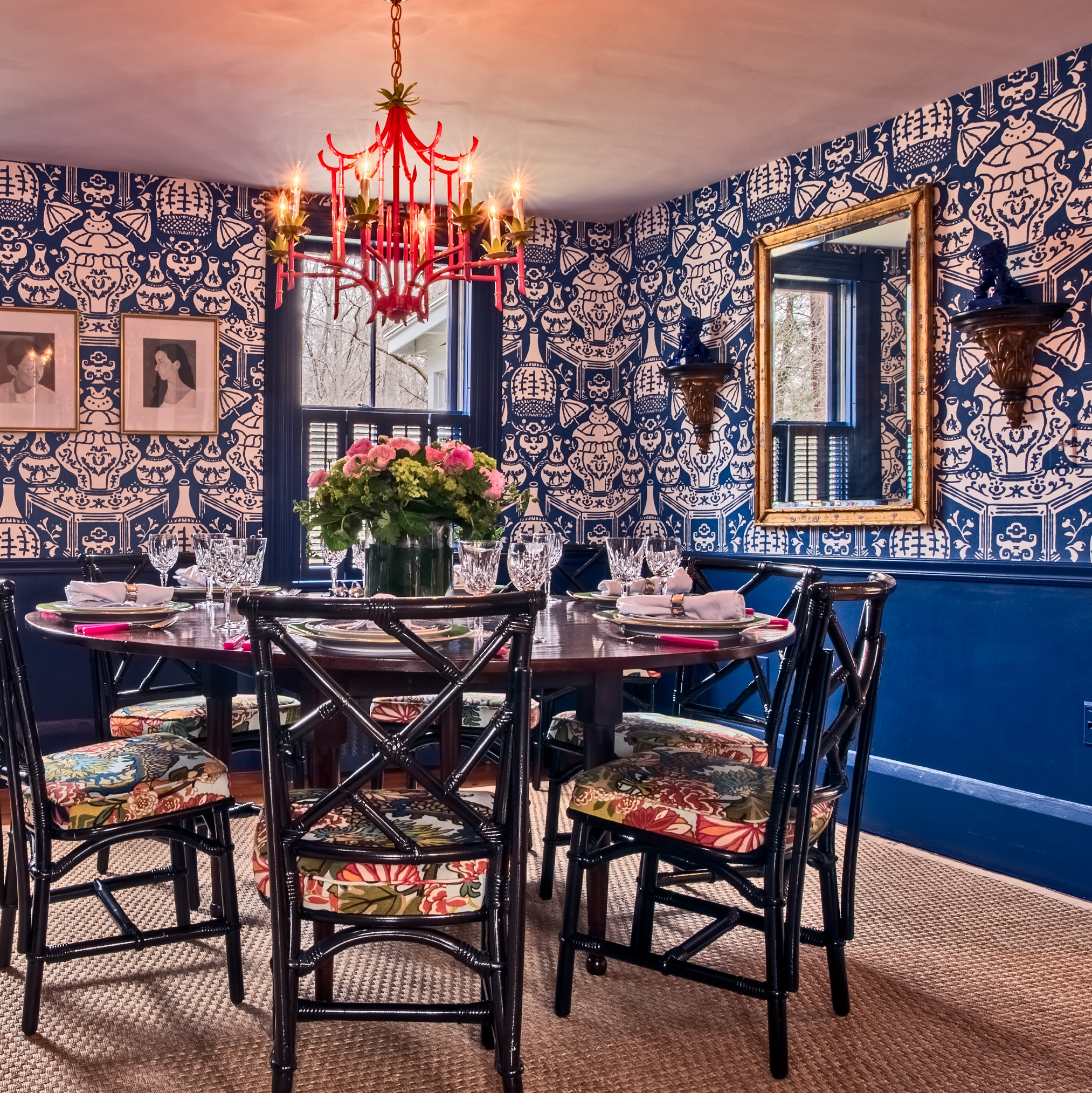 This is quite a cheerful and colorful dining room! The dragon upholstery on the lacquered bamboo chairs, the wallpaper, the pink pagoda chandelier, and the ceramics on the mantel are all Chinoiserie features.