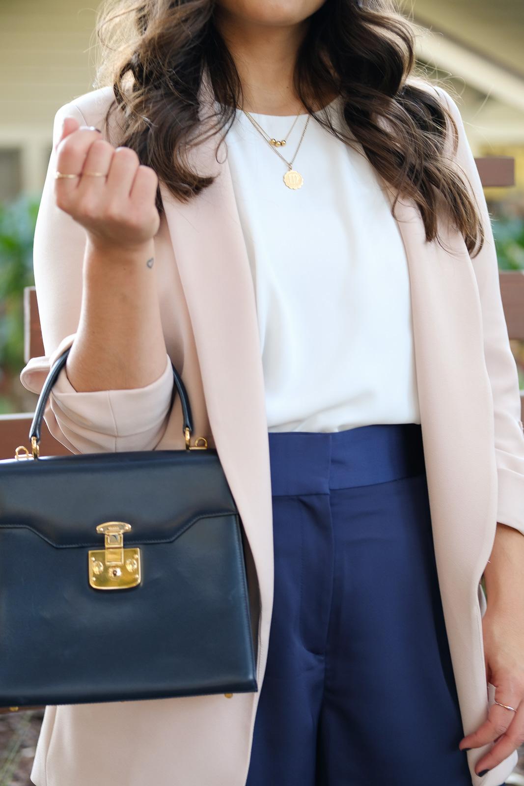 Pink blazer and navy handbag layered necklaces