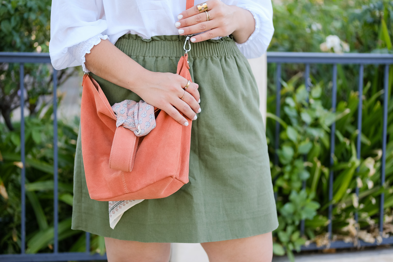layered gold rings and a green linen skirt