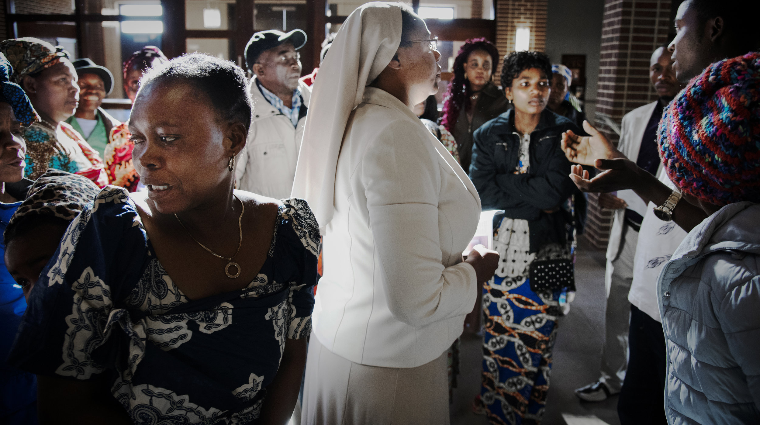 """Sister Joshua speaks with families of Congolese refugees following the Sunday mass at Holy Spirit Catholic Church. """"One thing I do know is that we have so much in common,"""" Sister Joshua said. Sometimes they do some things differently than the way i would do it, but sometimes I look at some of [their] cultures, and everything they do is exactly the same way, you know? So it is a privilege for me to welcome them as well."""""""