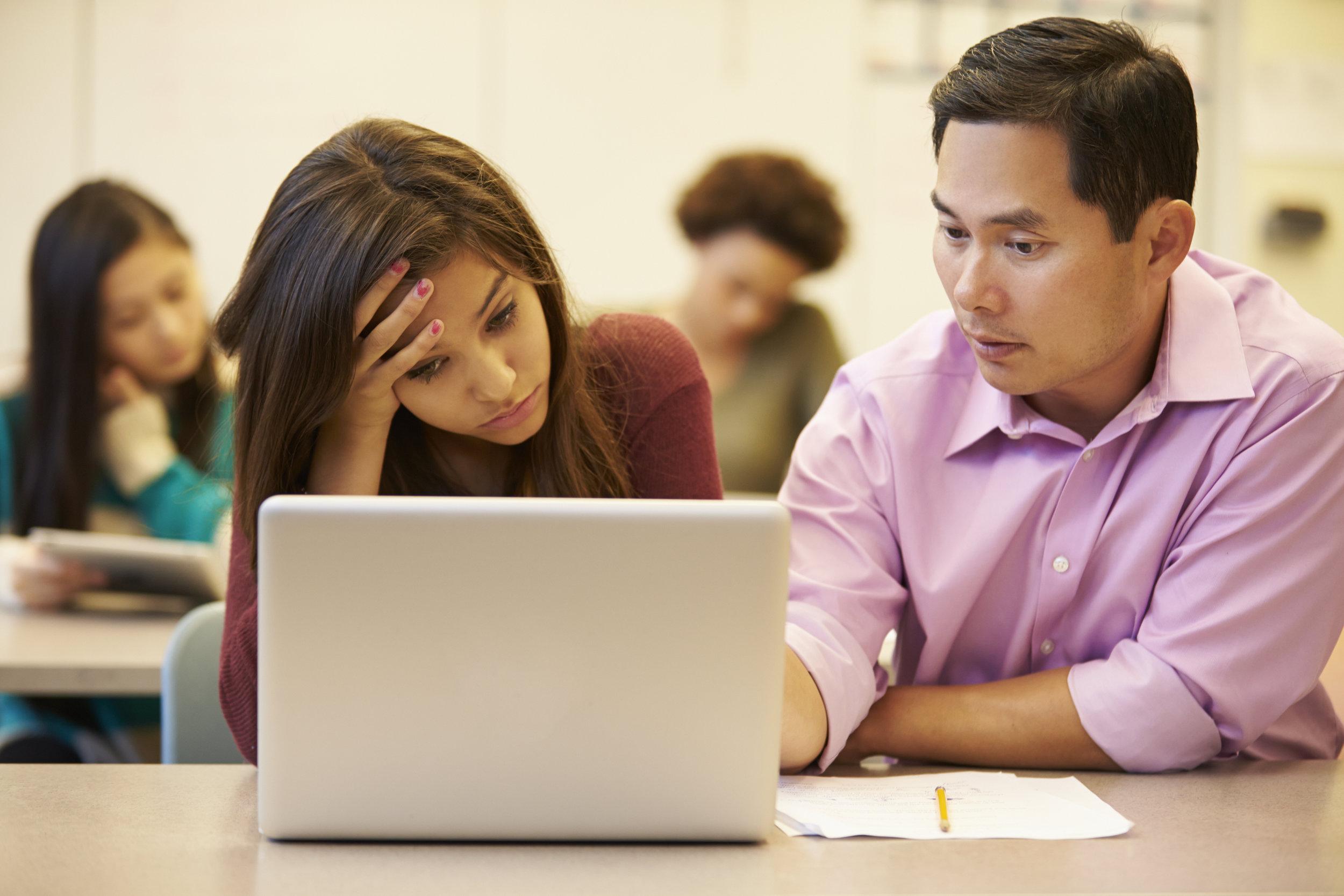 high-school-teacher-helping-stressed-pupil-in-PB73SRY.jpg