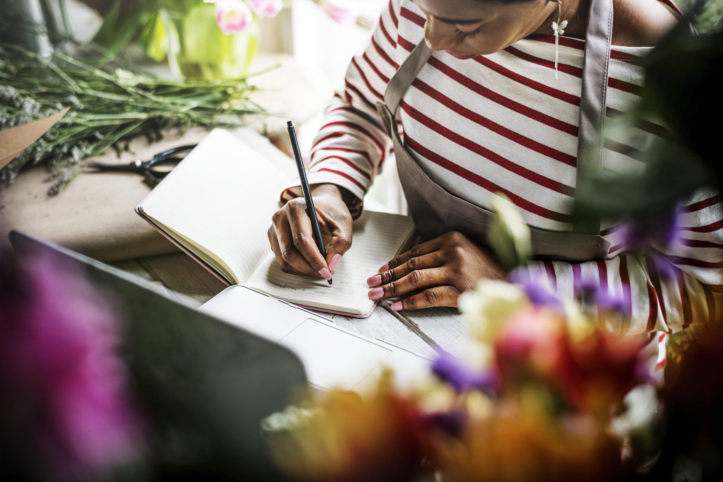 woman-sitting-writing-on-notebook-in-flower-shop-P7XFHGJ.jpg