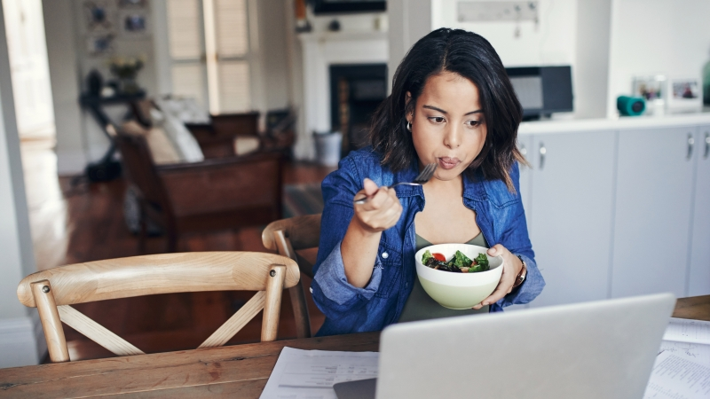 Young_woman_eating_at_desk_laptop_800_450.jpg