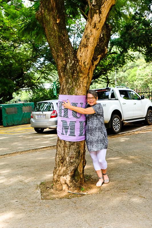 """Hier umarme ich die Jacaranda, die auf dem Parkplatz des Parks steht. Die Johannesburger Künstlerin Gail Scott Wilson, die wie ich bekennende Baumumarmerin ist, hat dem Baum ein """"Hug Me"""" geschenkt."""