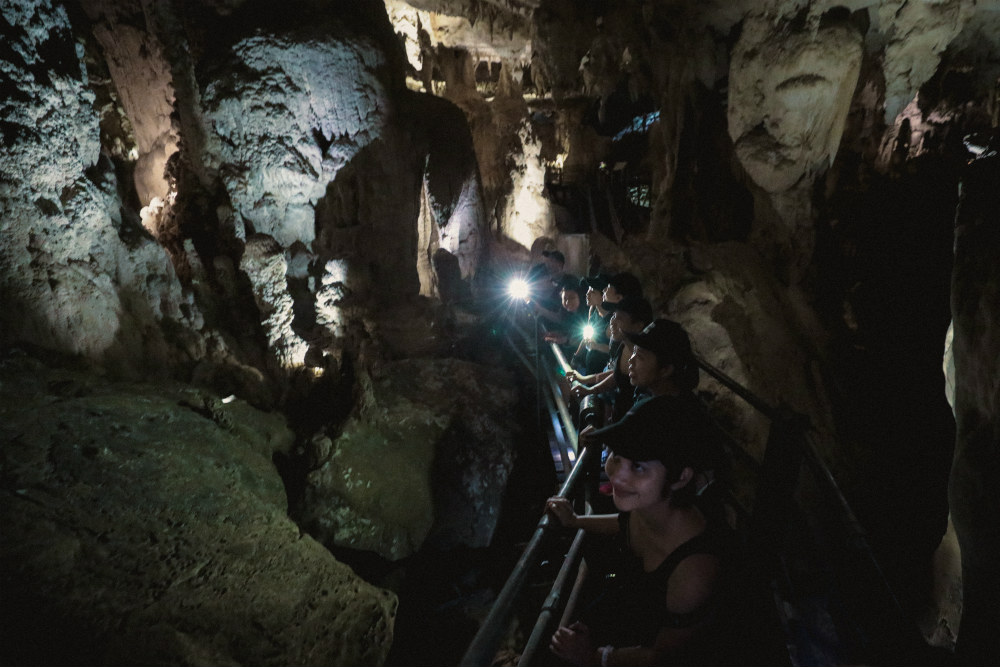 The show caves have lighting, but it helps to have a torch in hand to see the formations (and where you're stepping).