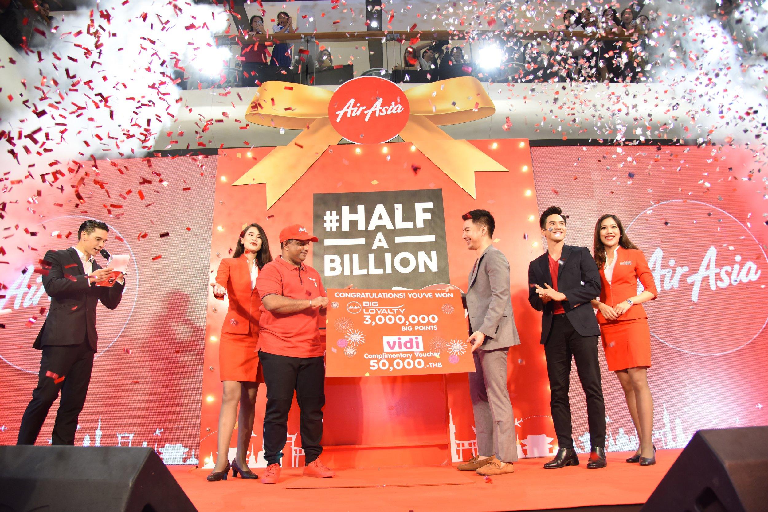 亚航第5亿名乘客Dr Panut Oprasertsawat(中间)从亚航集团首席执行员兼亚航长程集团联合首席执行员Tony Fernandes及泰国影星Pope Thanawat(右二)手中接过300百万亚航BIG积分、价值5万泰铢的 Vidi礼卷及终身免费机票。