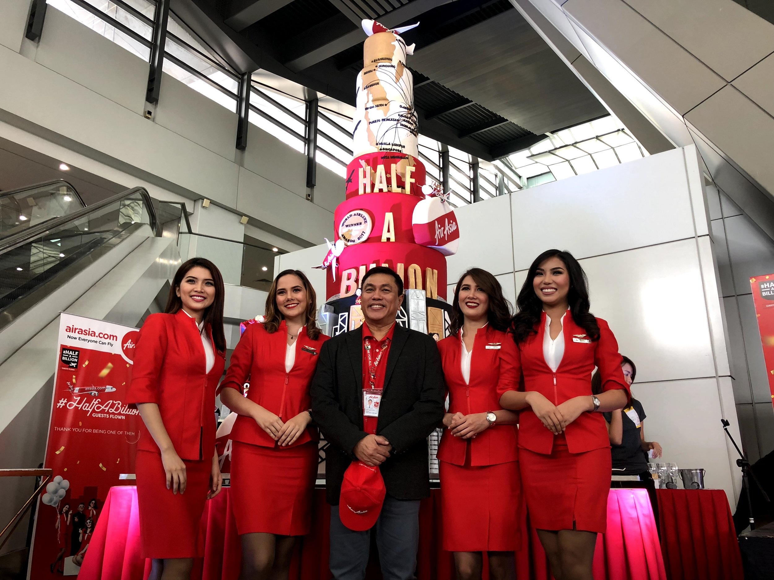 AirAsia Philippines CEO Capt. Dexter Comendador flanked by Cabin Crew at the Ninoy Aquino International Airport Terminal 3 with the 10-foot cake towering behind them.