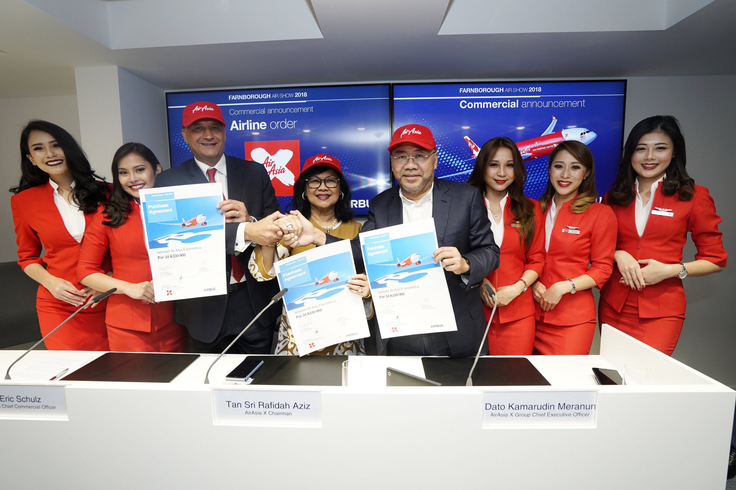 (왼쪽에서 세 번째부터 오른쪽으로) 에릭 슐츠 에어버스 CCO, 라피다 아지즈 에어아시아 엑스 회장, 카마루딘 메라눈 에어아시아 공동창업자 및 에어아시아 엑스 그룹 CEO가 2018 판버러 에어쇼에서 승무원들과 함께 항공기 주문 계약을 발표하고 있다.