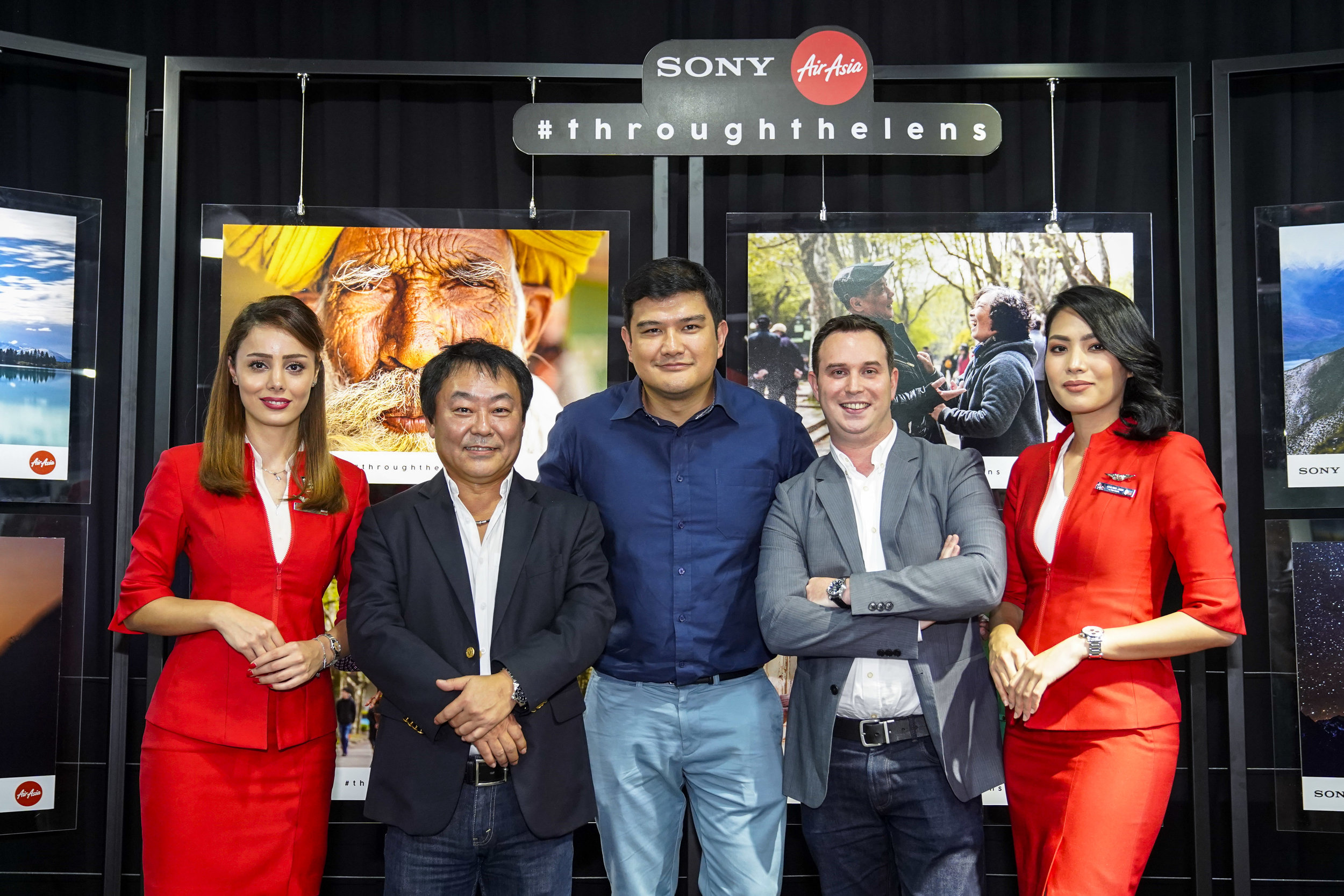 """Photo Caption: (From Left to Right) Sony Malaysia Managing Director Satoru Arai; AirAsia X Malaysia CEO Benyamin Ismail and AirAsia X Group Head of Commercial Barry Klipp flanked by cabin crew at the launch of """"Through the Lens"""" to search for a joint ambassador for the brands."""