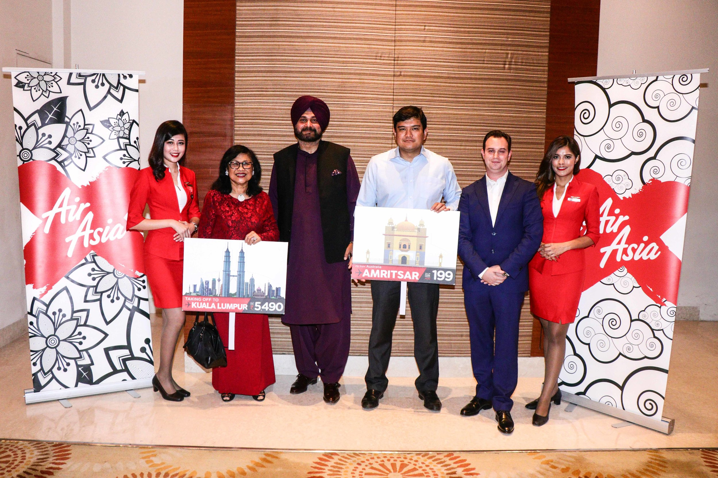 Photo Caption: (From left to right) AirAsia X chairman Tan Sri Rafidah Aziz (second from left)  poses with Punjab Tourism and Cultural  Affairs Minister Shri Navjot Singh Sidhu (third from left), AirAsia X CEO Benyamin Ismail and AirAsia X Group Head of Commercial Barry Klipp after a special press conference in Amritsar in conjunction with AirAsia's inaugural flight today. They are flanked by cabin crew of the inaugural service that took flight from Kuala Lumpur to the holy city on yesterday (16 August 2018).