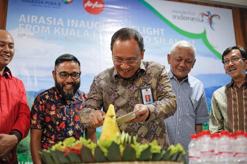 Sekretaris Kementerian Koordinator Bidang Kemaritiman Agus Purwoto meresmikan penerbangan perdana AirAsia rute Kuala Lumpur - Silangit bersama CEO AirAsia Malaysia Riad Asmat (kedua dari kiri), Bupati Tapanuli Utara Nikson Nababan (paling kiri), Bupati Toba Samosir Edward Darwin Siagian (kedua dari kanan), dan Staf Khusus Menteri Pariwisata Judi Rifajantoro (paling kanan) di Bandara Internasional Silangit hari ini.
