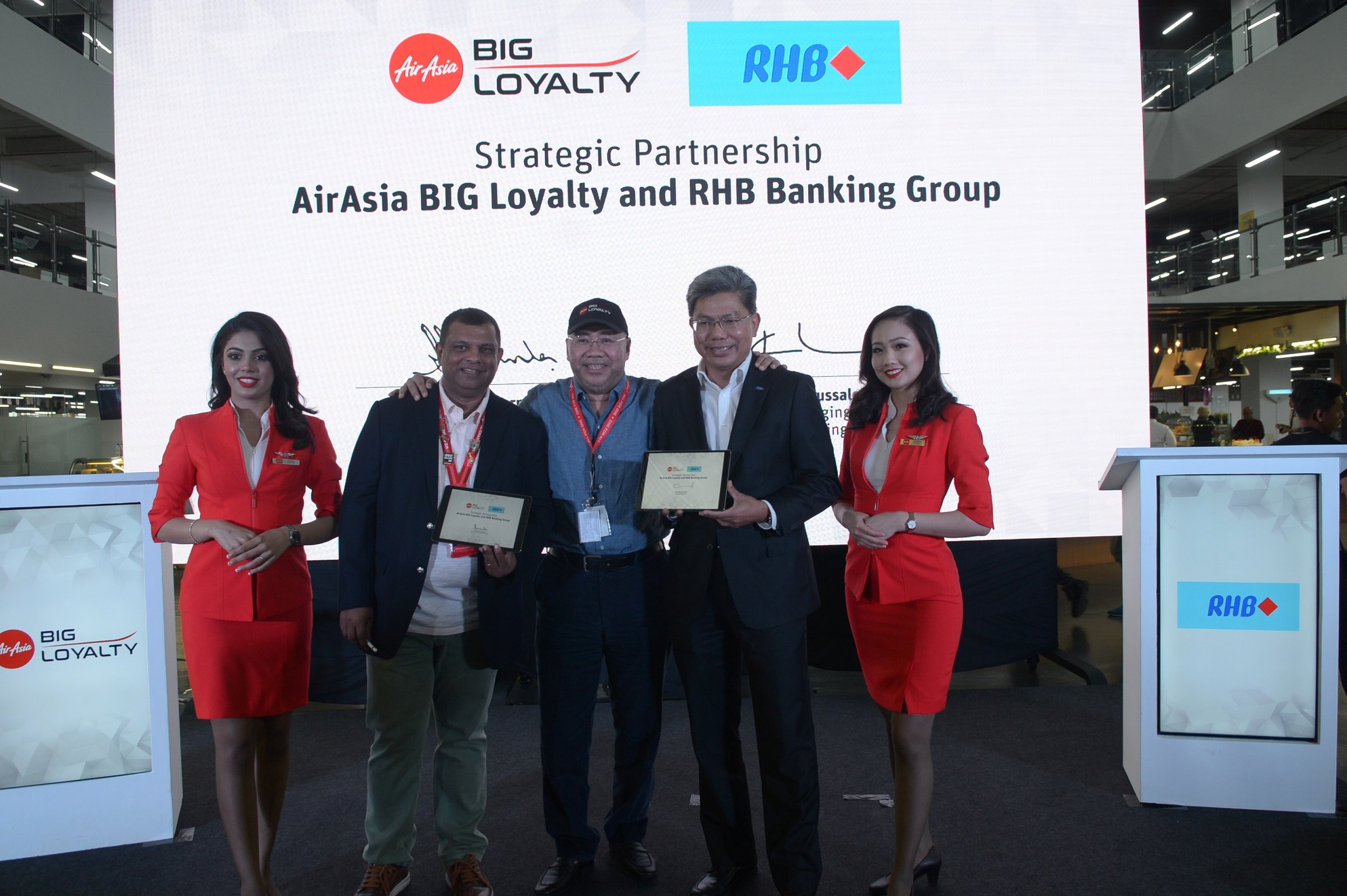 Directors of BIG Loyalty Sdn Bhd Tan Sri Tony Fernandes (second from left) and Datuk Kamarudin Meranun (centre) sealing the partnership with Group Managing Director of RHB Banking Group Dato' Khairussaleh Ramli (second from right).