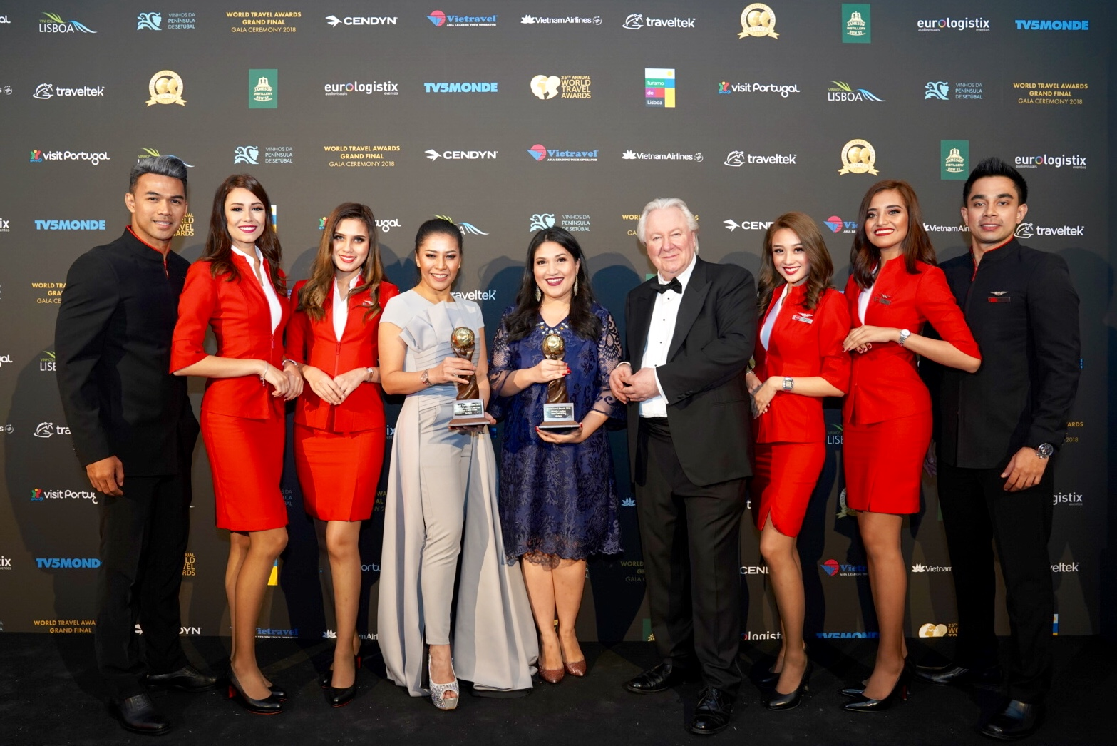 AirAsia Group Head of Cabin Crew Suhaila Hassan (centre left) and AirAsia Group Head of Communications Audrey Progastama Petriny (centre) accepted the World's Leading Low-Cost Airline and World's Leading Low-Cost Airline Cabin Crew awards from President and Founder of World Travel Awards Graham Cooke (centre right), flanked by AirAsia cabin crew.