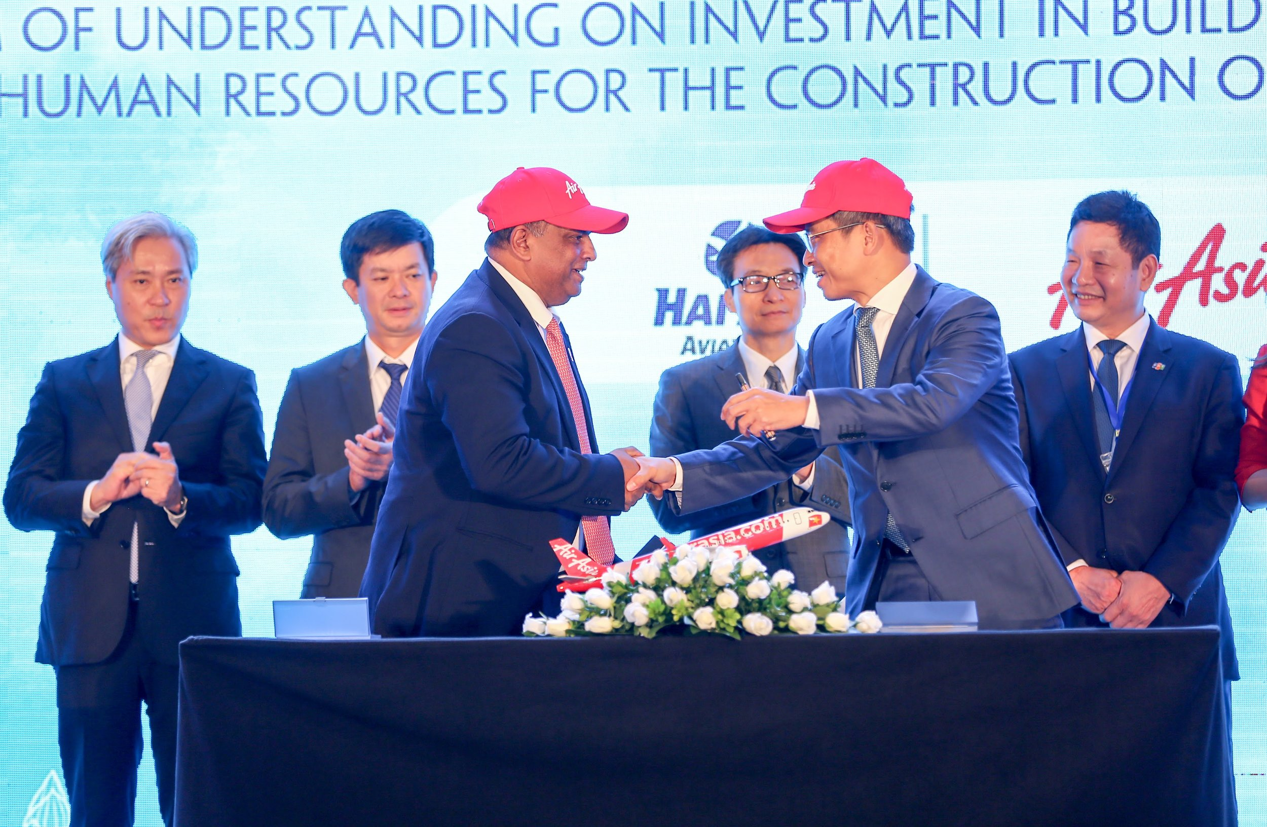 Photo Caption:  AirAsia Group CEO Tony Fernandes (front centre left) shakes hands with Tran Trong Kien, CEO of Thien Minh Travel Joint Stock Company CEO and General Director of Hai Au Aviation Joint Stock Company, after the memorandum signing witnessed by Vietnamese Deputy Prime Minister Vu Duc Dam (centre right) and Vietnamese Deputy Minister of Culture, Sports and Tourism Le Quang Tung (centre left), flanked by the Vice Chairmen of the Vietnamese Advisory Council to the Prime Minister on Administrative Procedures Reform, VinaCapital Group CO-Founder and CEO Don Lam (far left) and FPT Corporation Co-Founder, Chairman and CEO Truong Gia Binh (far right), who is also Chairman of Vietnam's Private Sector Development Committee.