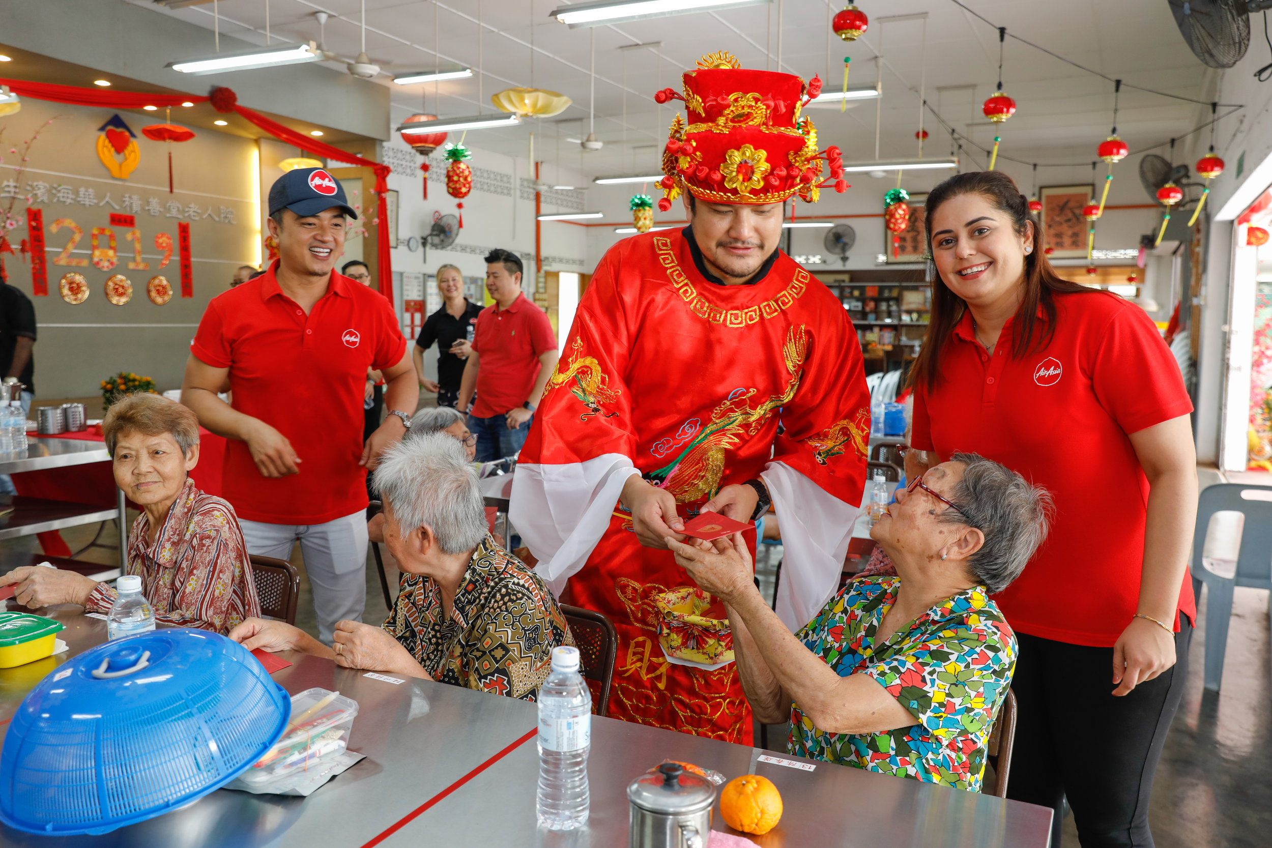 Photo caption:  AirAsia X Malaysia CEO Benyamin Ismail decked in God of Prosperity costume distributes ang pau to the residents of Chik Sin Thong Klang & Pantai Old Folks' home.