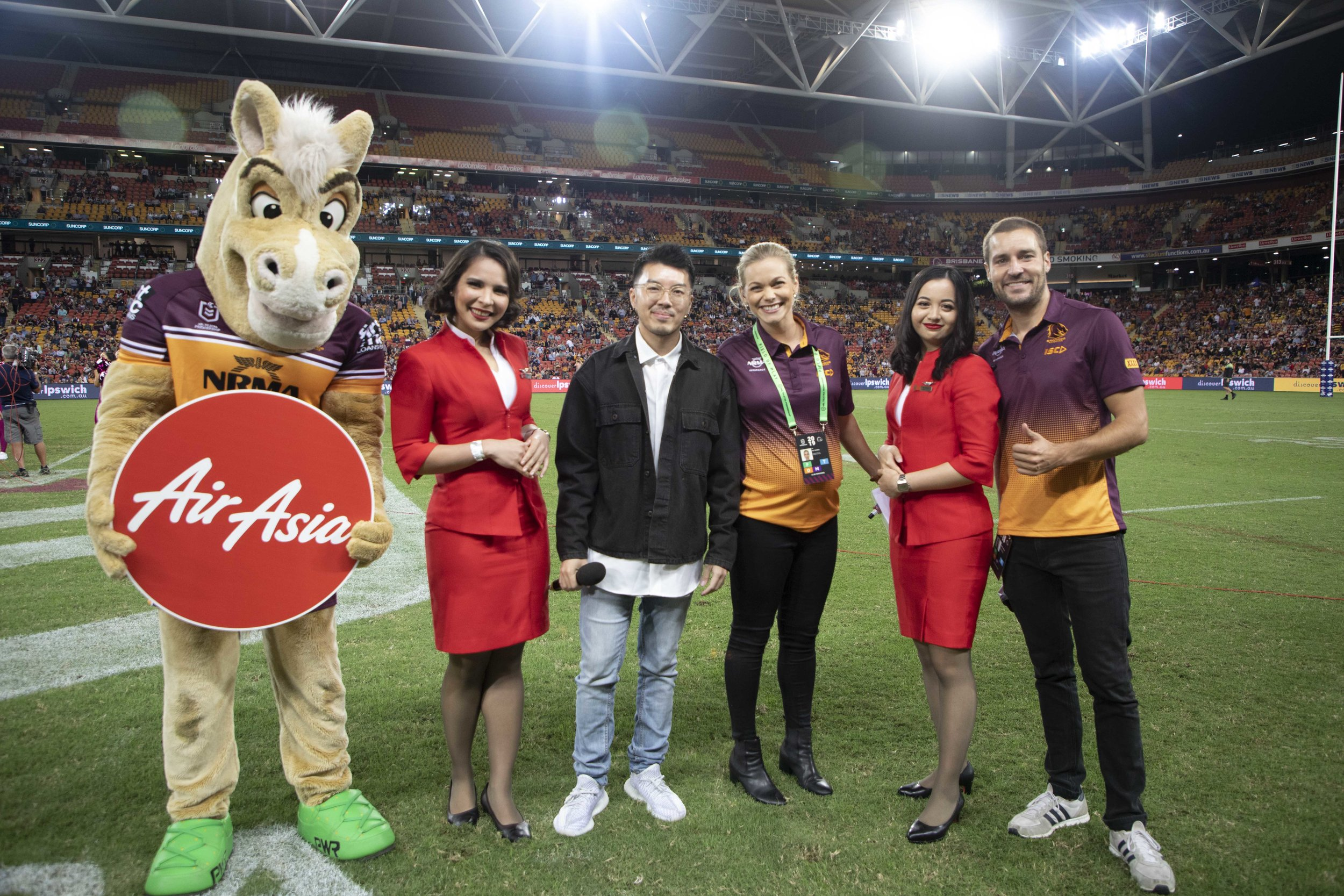 Photo Caption:  AirAsia Group Head of Branding Rudy Khaw (3rd from Left) with Buck the Brisbane Bronco, AirAsia Cabin Crew and Brisbane Bronco's Announcers Pip Russell and Dan Antsey at Suncorp Stadium