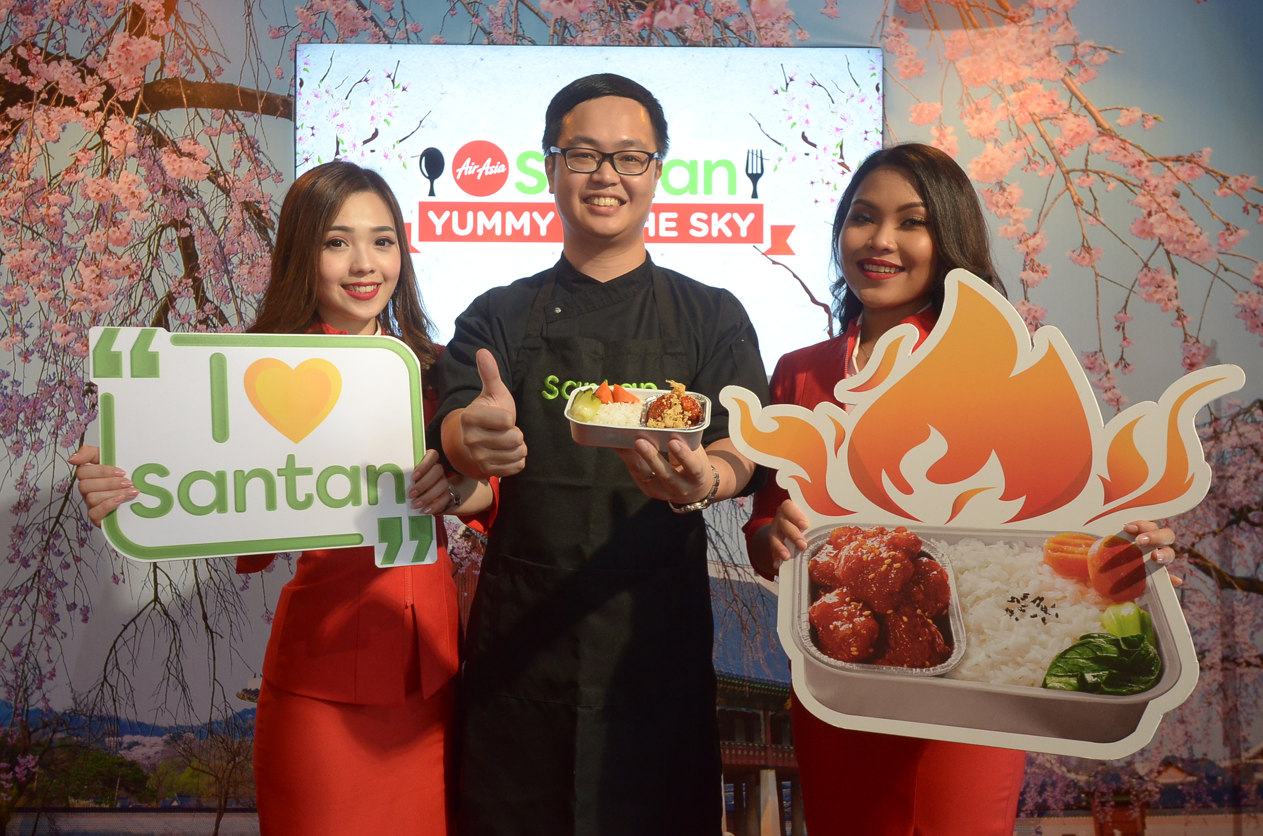 AirAsia Resident Chef, Chef Calvin Soo introducing the new Santan Celebrity Chef Series Meal - Chef Hong's Korean Sweet & Spicy Chicken flanked by AirAsia cabin crews.