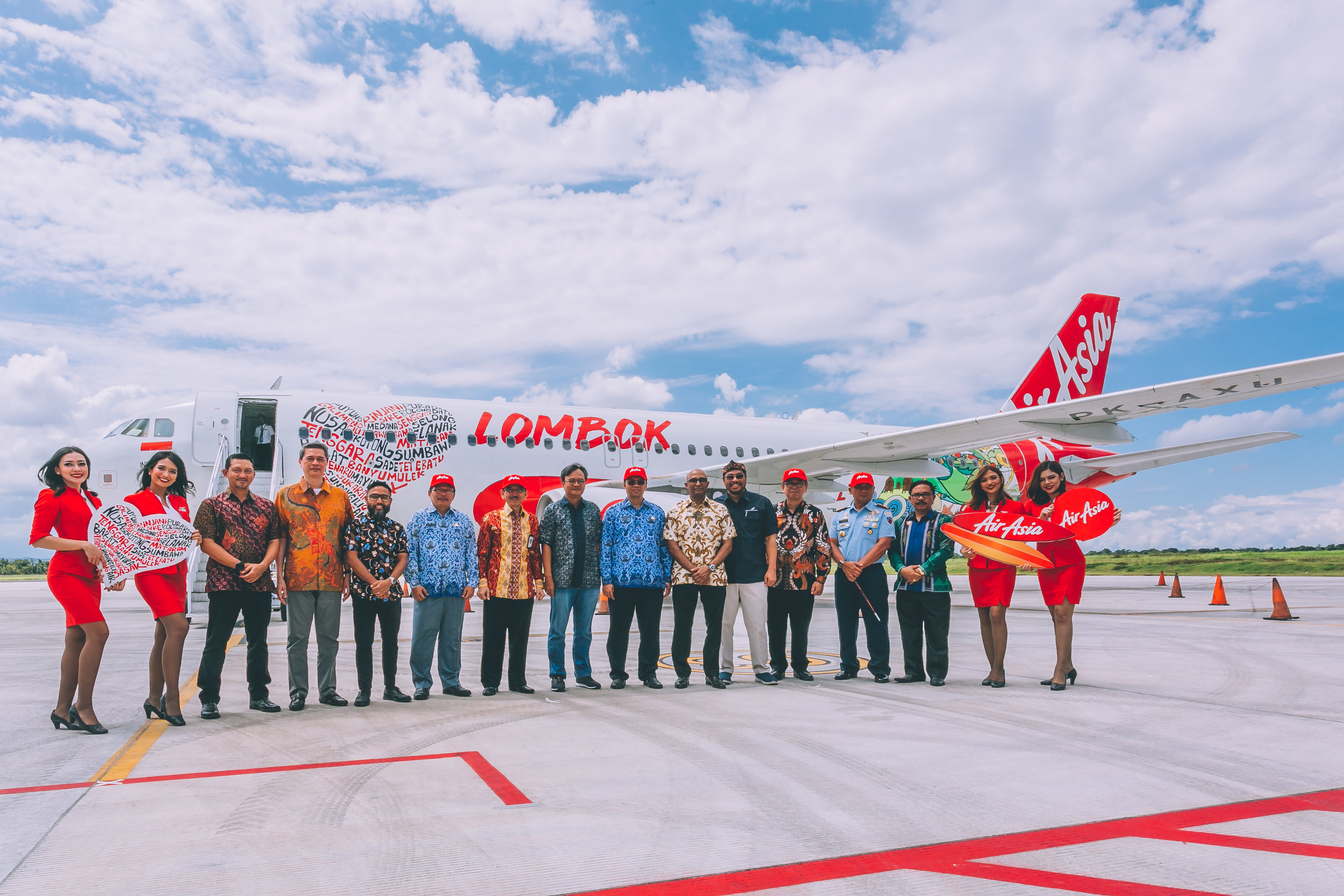 """Photo Caption:  West Nusa Tenggara Governor Dr H Zulkifliemansyah SE Msc (ninth from left), flanked by AirAsia Deputy Group CEO (Airlines) Bo Lingam and Angkasa Pura I Director of International Connectivity and Business Development Sardjono Jhonny Tjitrokusumo to his left, AirAsia Indonesia CEO Dendy Kurniawan and Special Staff to Indonesia's Minister of Tourism Judi Rifajantoro to his right, and AirAsia Thailand Executive Chairman Tassapon Bijleveld (fourth from left) and AirAsia Malaysia CEO Riad Asmat (fifth from left) in front of an AirAsia A320 aircraft with """"I Love Lombok"""" livery."""