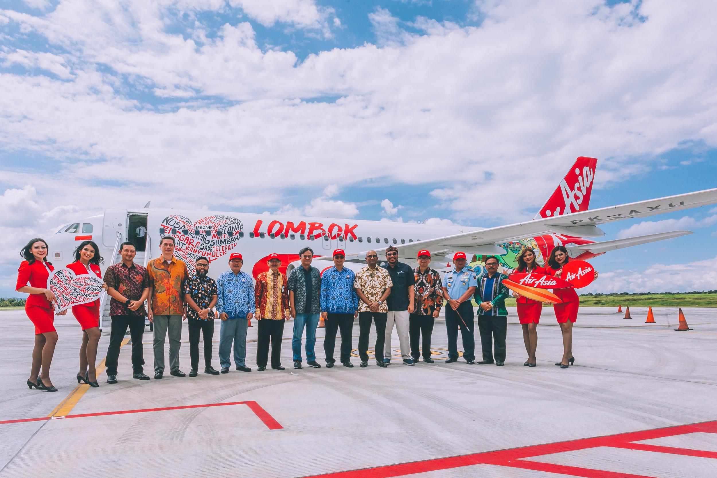 """Keterangan Gambar:  Gabenor Nusa Tenggara Barat Dr H Zulkifliemansyah SE Msc (sembilan dari kiri), diiringi oleh Timbalan Ketua Pegawai Eksekutif Kumpulan AirAsia (Penerbangan) Bo Lingam dan Pengarah Hubungan dan Pembangunan Perniagaan Antarabangsa Angkasa Pura I Sardjono Jhonny Tjitrokusumo (kiri), Ketua Pegawai Eksekutif AirAsia Indonesia Dendy Kurniawan dan Kakitangan Khas kepada Menteri Pelancongan Indonesia Judi Rifajantoro (di sebelah kanan), dan Pengerusi Eksekutif AirAsia Thailand Tassapon Bijleveld (empat dari kiri) dan Ketua Pegawai Eksekutif AirAsia Malaysia, Riad Asmat (lima dari kiri) di hadapan pesawat AirAsia A320 dengan slogan """"I Love Lombok"""" ."""