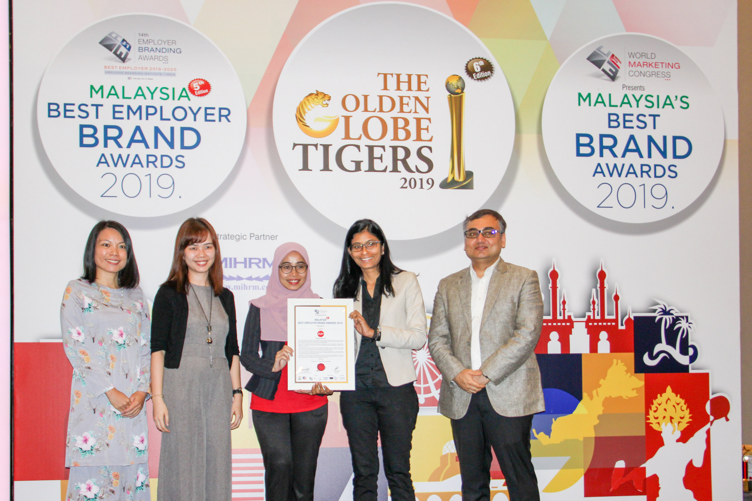 L-R (dua dari kiri): Pengurus Perkhidmatan People AirAsia Mandy Pui, Eksekutif Perkhidmatan People Nur Farhana Ibrahim dan Ketua Bahagian Culture AirAsia Renuka Kunathevan menerima Anugerah Jenama Majikan Terbaik Malaysia