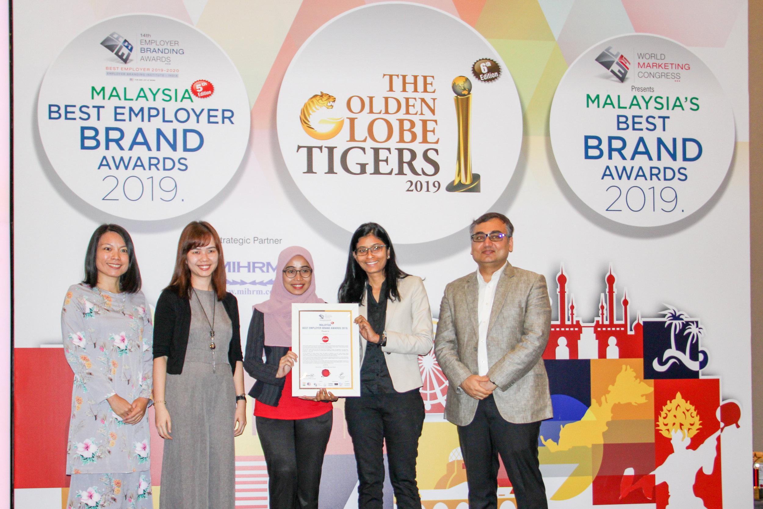 左-右 (最后第二位起):亚航人力服务经理Mandy Pui、亚航人力服务执行员Nur Farhana Ibrahim、马来西亚亚航文化部主管Renuka Kunathevan接下奖项